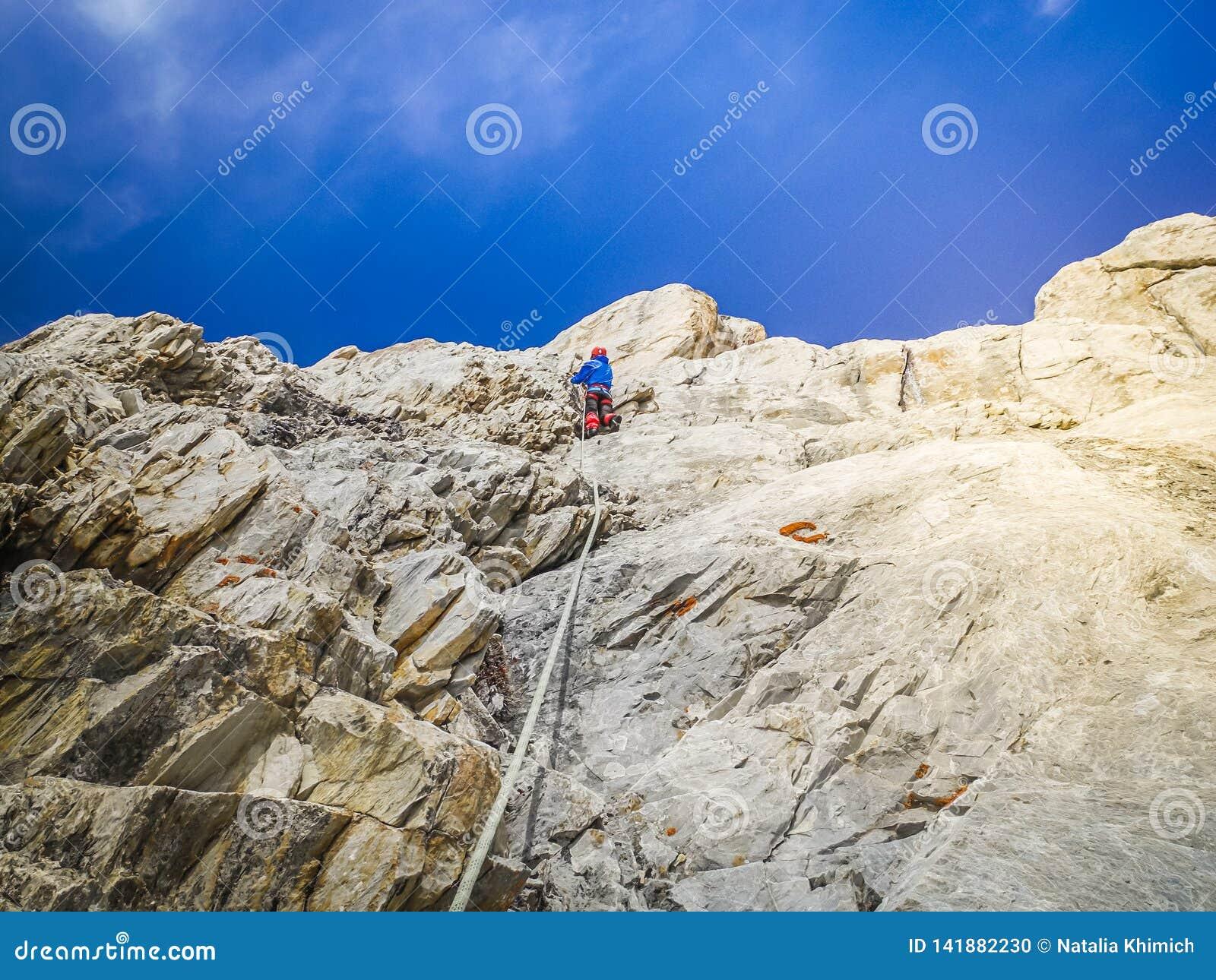 Ένας ορειβάτης ατόμων αναρριχείται στις δύσκολες προεξοχές στην κορυφή Η έννοια της ακραίων αναψυχής και της περιπέτειας