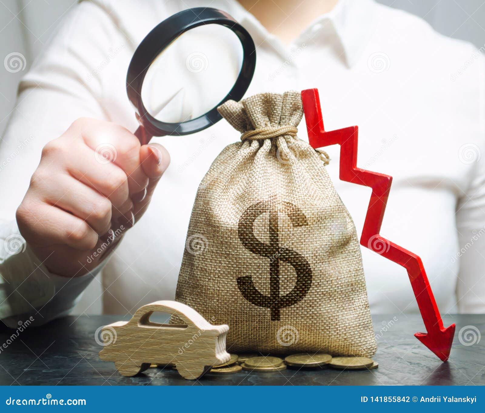 Ένας διευθυντής κρατά μια ενίσχυση - γυαλί πέρα από μια τσάντα χρημάτων, ένα αυτοκίνητο και ένα κάτω βέλος Μειωμένο κόστος της συ