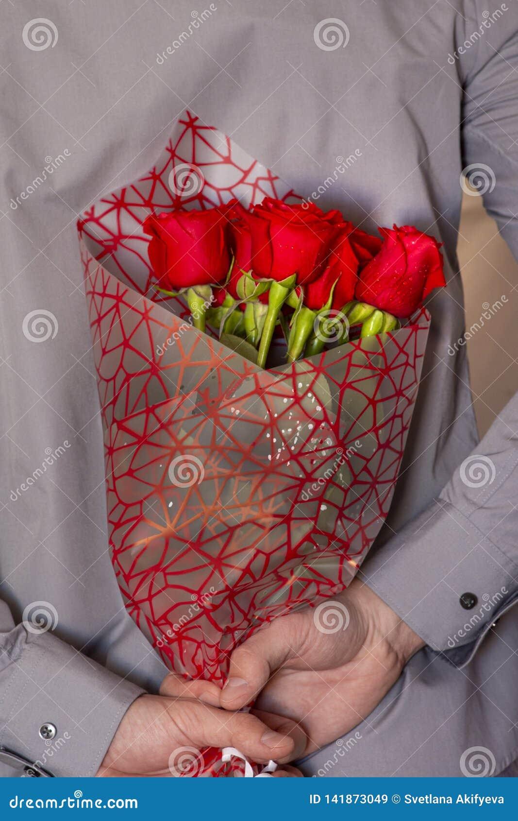 Ένα άτομο που κρατά μια ανθοδέσμη των κόκκινων τριαντάφυλλων
