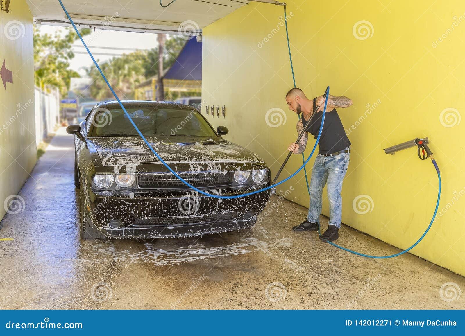 Ένα άτομο που πλένει το αυτοκίνητό του στον κόλπο αυτοκίνητο-πλυσίματος