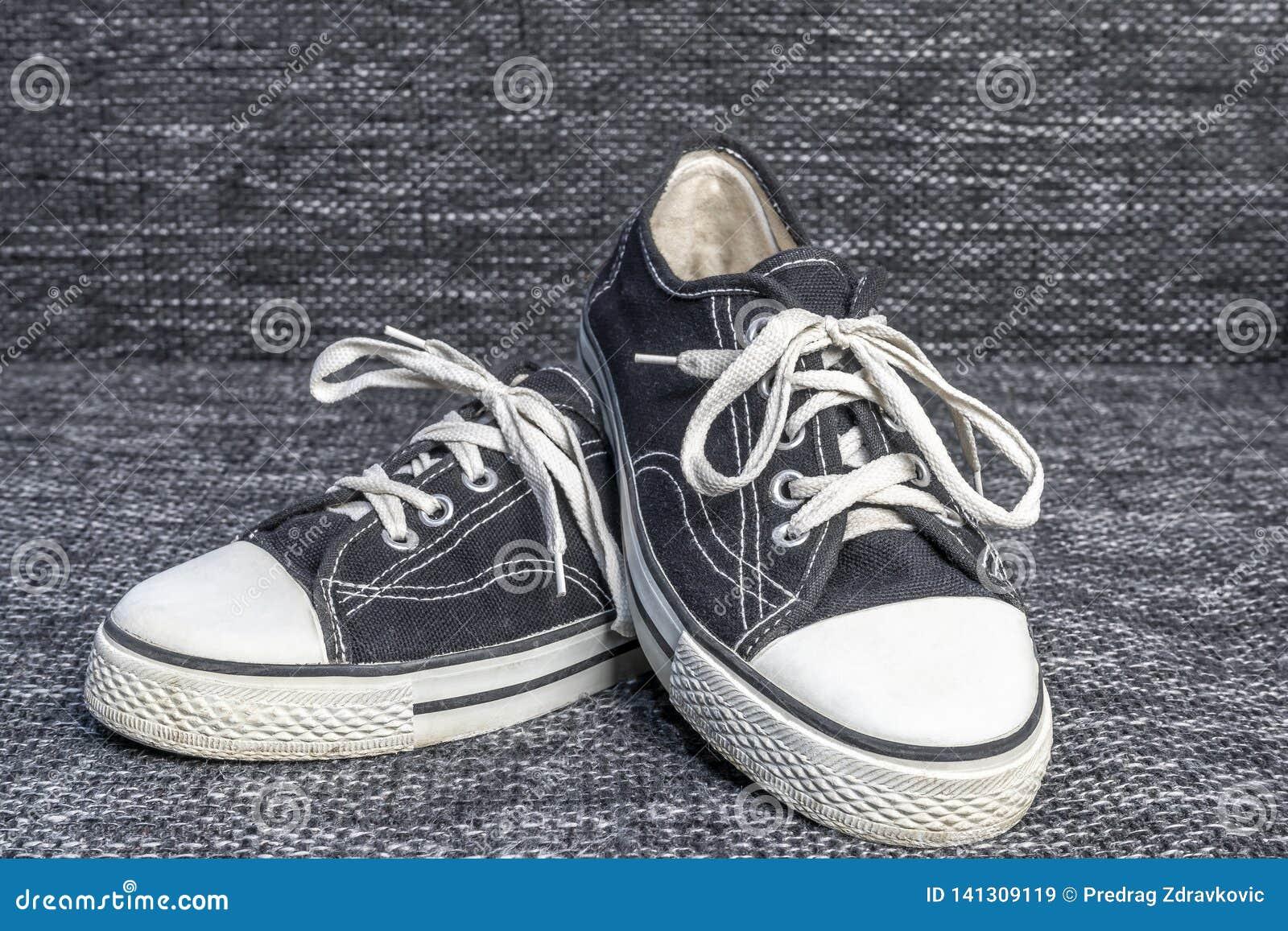 Ένα ζευγάρι των παλαιών πάνινων παπουτσιών σε ένα υπόβαθρο καμβά