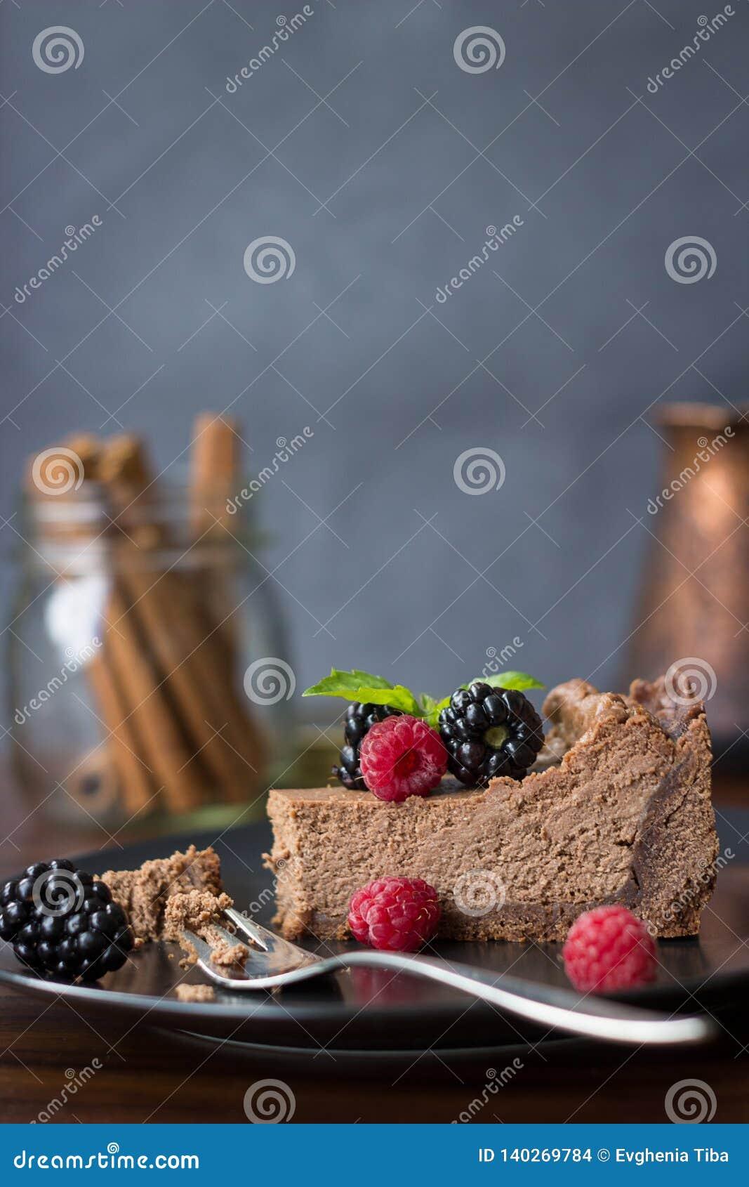 Ένα κομμάτι cheesecake σοκολάτας με τα βατόμουρα και τα σμέουρα