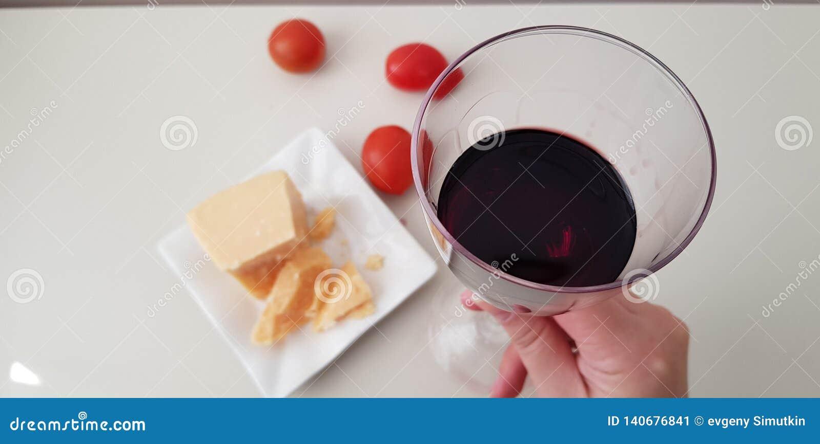 Ένα κορίτσι κρατά το γυαλί της κόκκινης αμπέλου
