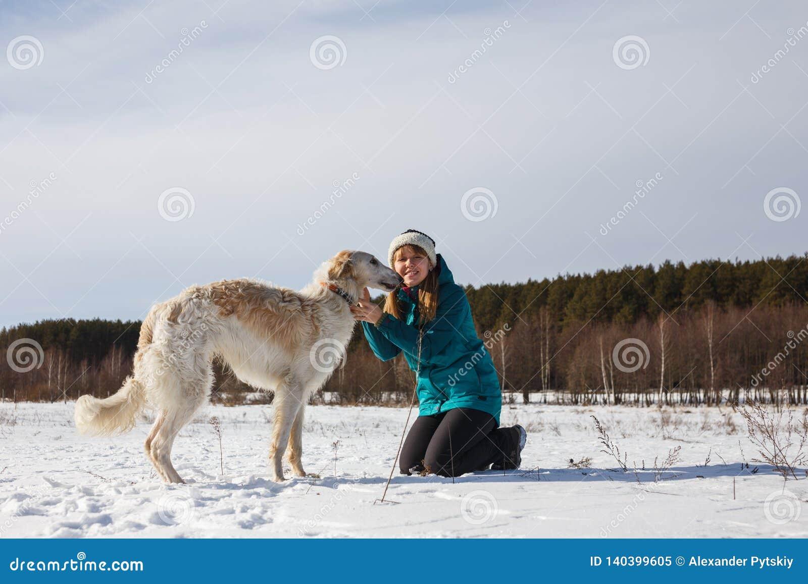 Ένα κορίτσι σε ένα πράσινο σακάκι σκι στα γόνατά της και ένα ρωσικό λευκό κυνηγόσκυλο σε έναν χιονώδη τομέα τον ηλιόλουστο χειμών
