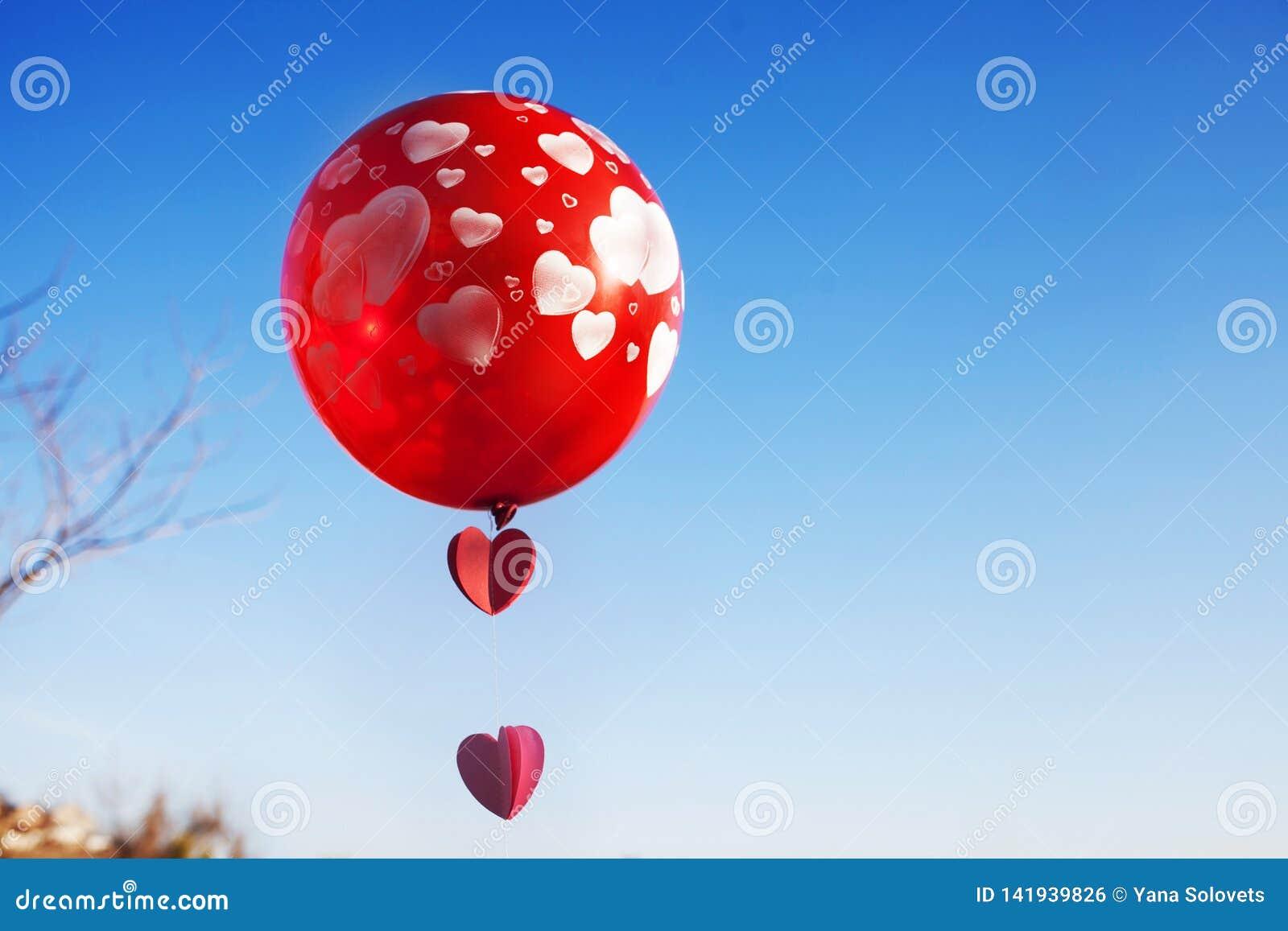 Ένα μικρό κορίτσι με το κόκκινο μπαλόνι στο μπλε ουρανό