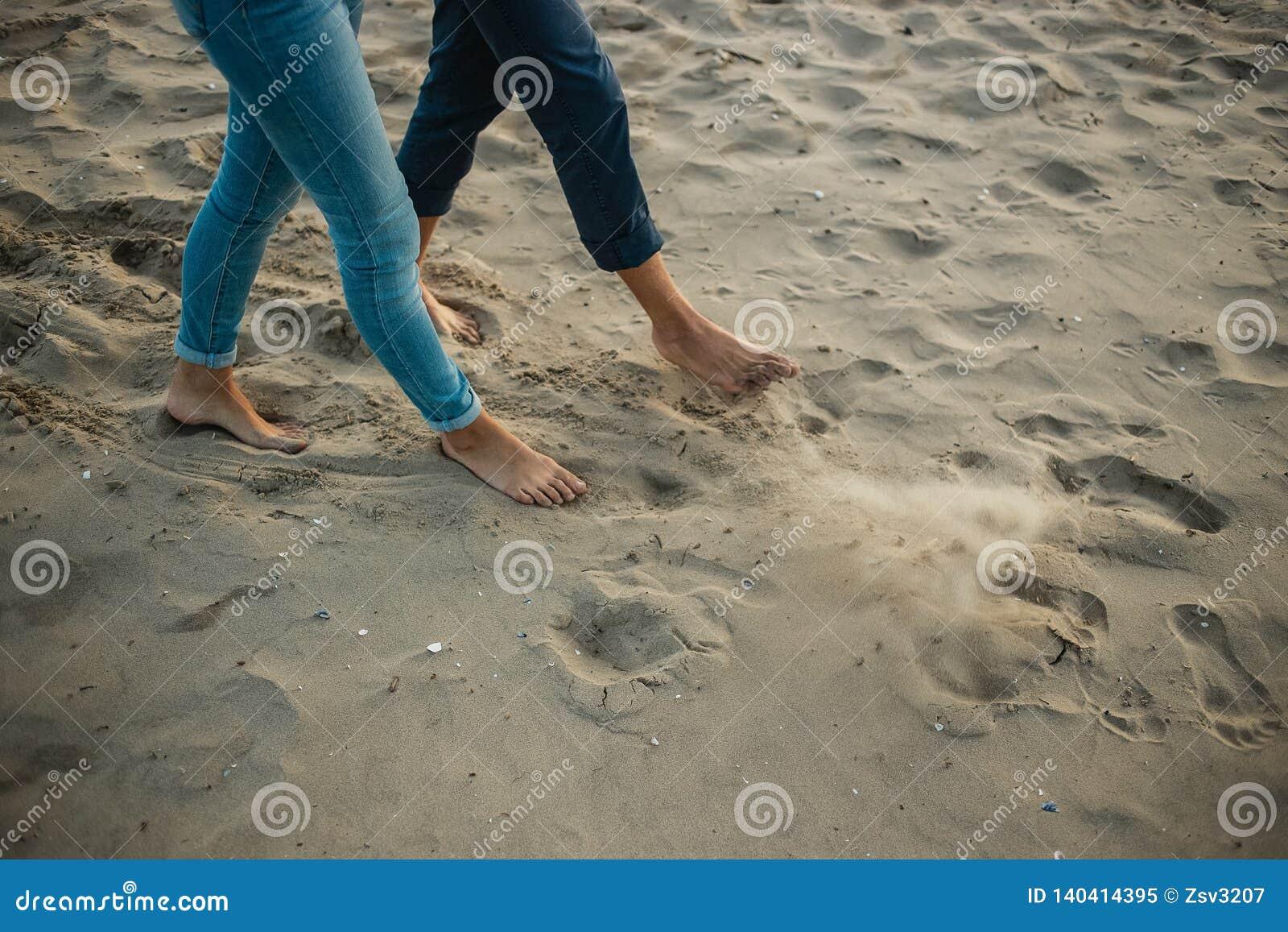 Ένα νέο ζεύγος έχει τη διασκέδαση και περπατά στην ακτή θάλασσας Τα πόδια κλείνουν επάνω Ρομαντική ημερομηνία στην παραλία