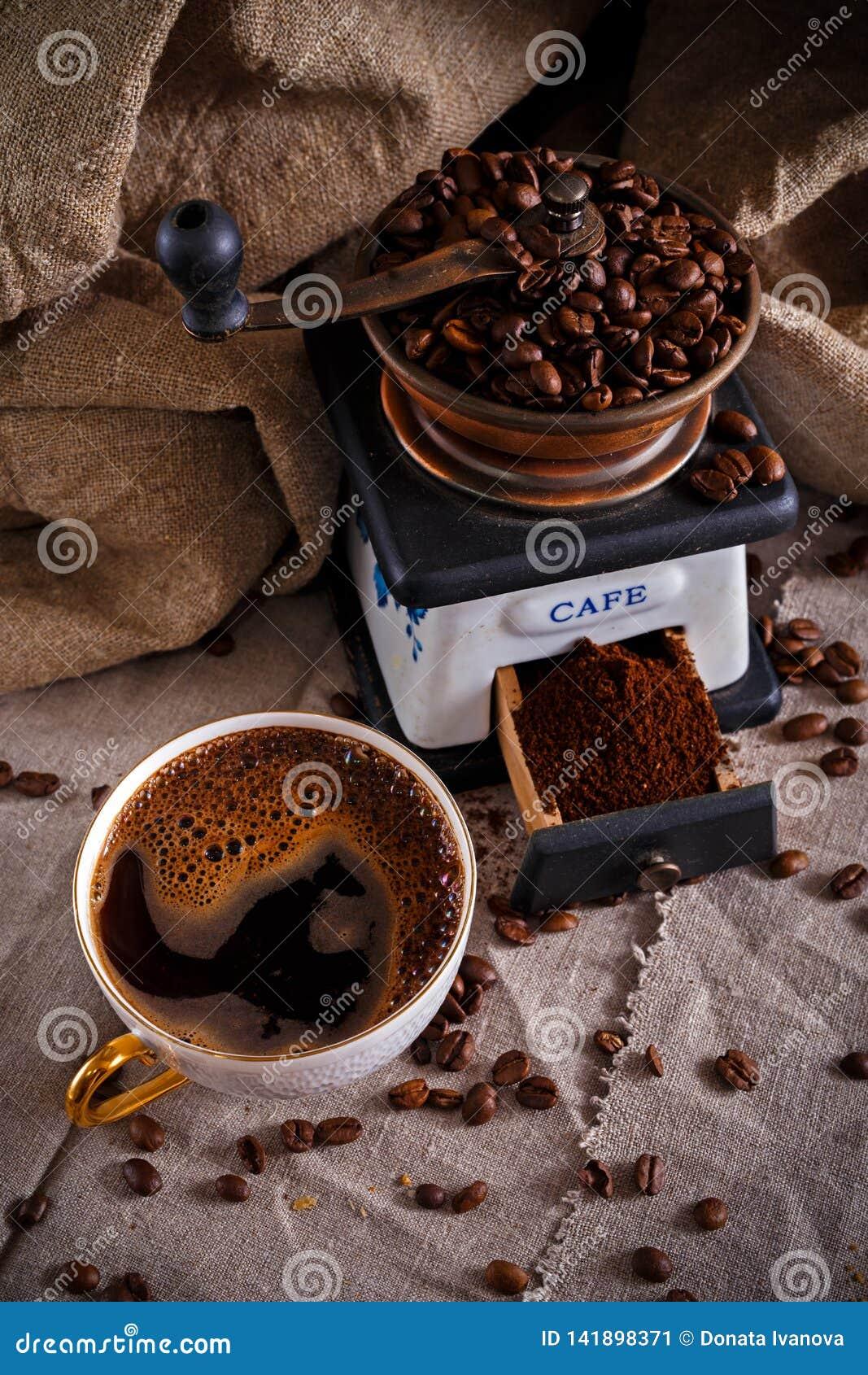 Ένα φλυτζάνι του μαύρου καφέ, ενός μύλου καφέ και διεσπαρμένων φασολιών καφέ σε έναν πίνακα που καλύπτεται με burlap
