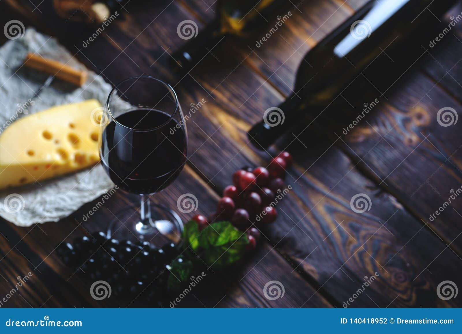 Ένα ποτήρι του τυριού και των σταφυλιών κόκκινου κρασιού