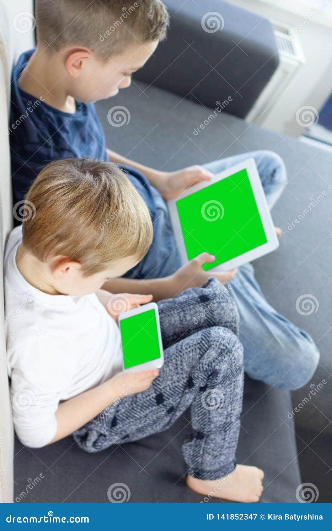 Αγόρια που κάθονται και που χρησιμοποιούν την ταμπλέτα και το κινητό έξυπνο τηλέφωνο με την πράσινη οθόνη στο σπίτι