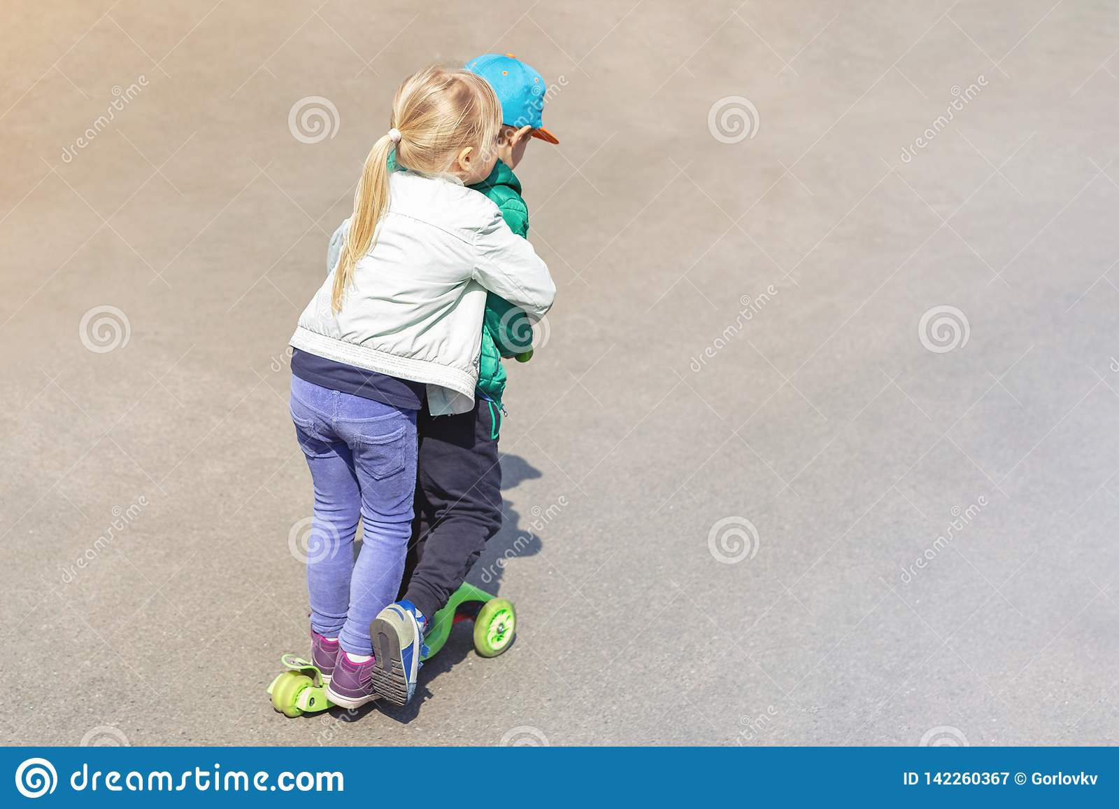 Αγόρι και κορίτσι δύο frineds που έχουν τη διασκέδαση που οδηγά ένα μηχανικό δίκυκλο μαζί ταυτόχρονα Αμφιθαλείς, αδελφός και αδελ