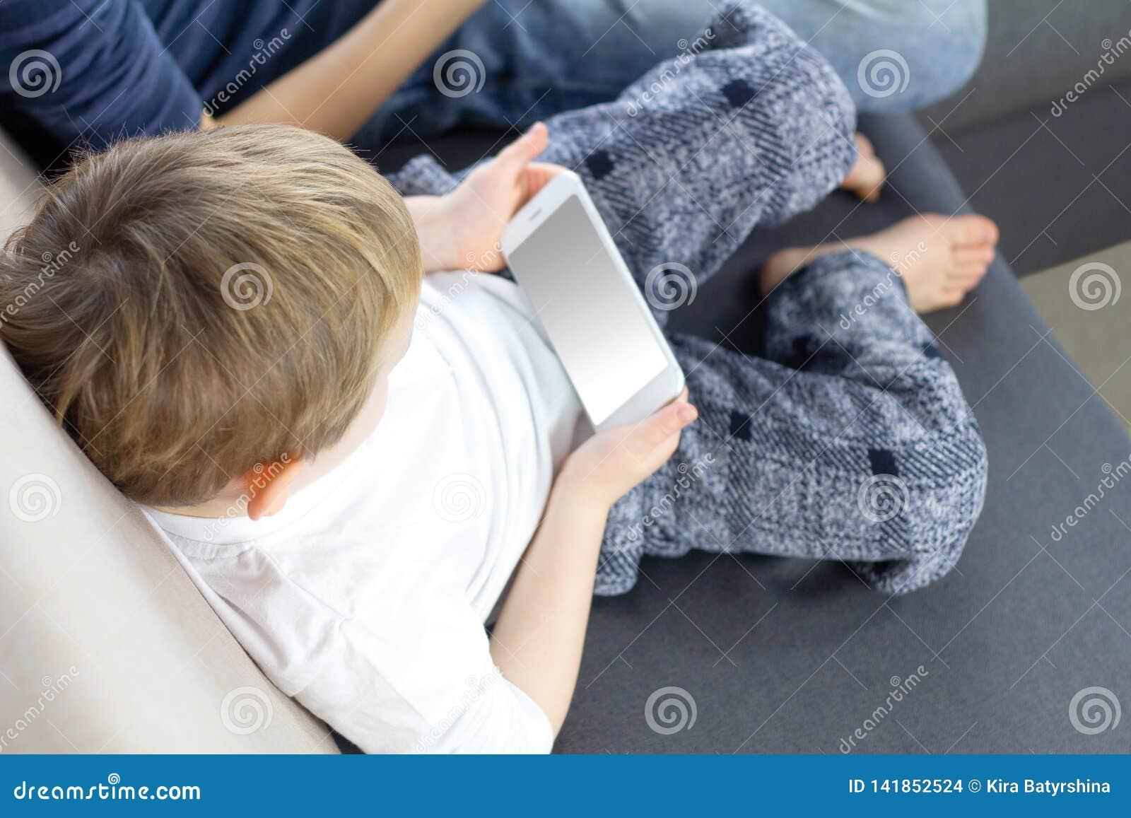 Αγόρι παιδιών που χρησιμοποιεί το κινητό τηλέφωνο Smartphone στα χέρια παιδιών Παιχνίδι μικρών παιδιών με το κινητό τηλέφωνο Έννο