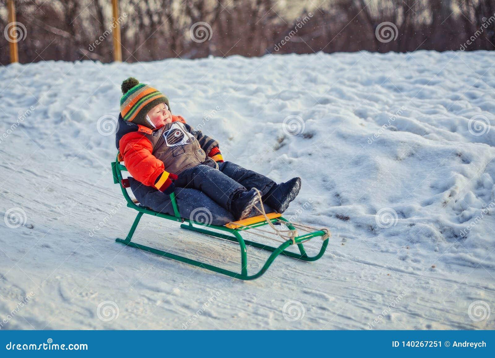 Αγόρι που απολαμβάνει έναν γύρο ελκήθρων Παιδιά που οδηγούν ένα έλκηθρο Παιδικό παιχνίδι υπαίθρια στο χιόνι Έλκηθρο παιδιών στο χ
