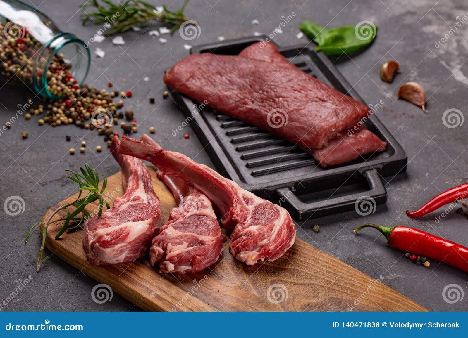 Ακατέργαστο φρέσκο πρόβειο κρέας κρέατος στα καρυκεύματα Chesno και Rosemary κόκκαλων σε ένα μαύρο υπόβαθρο