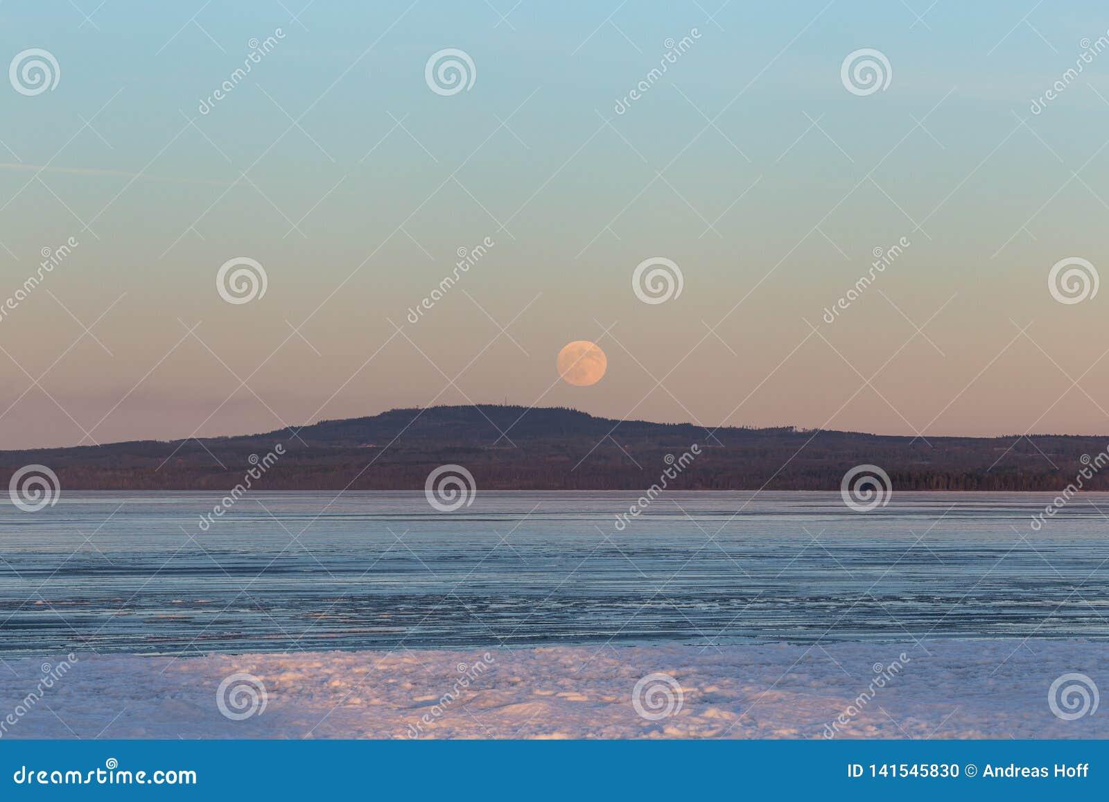 Ανατολή του φεγγαριού πέρα από το βουνό Kinnekulle στη Σουηδία