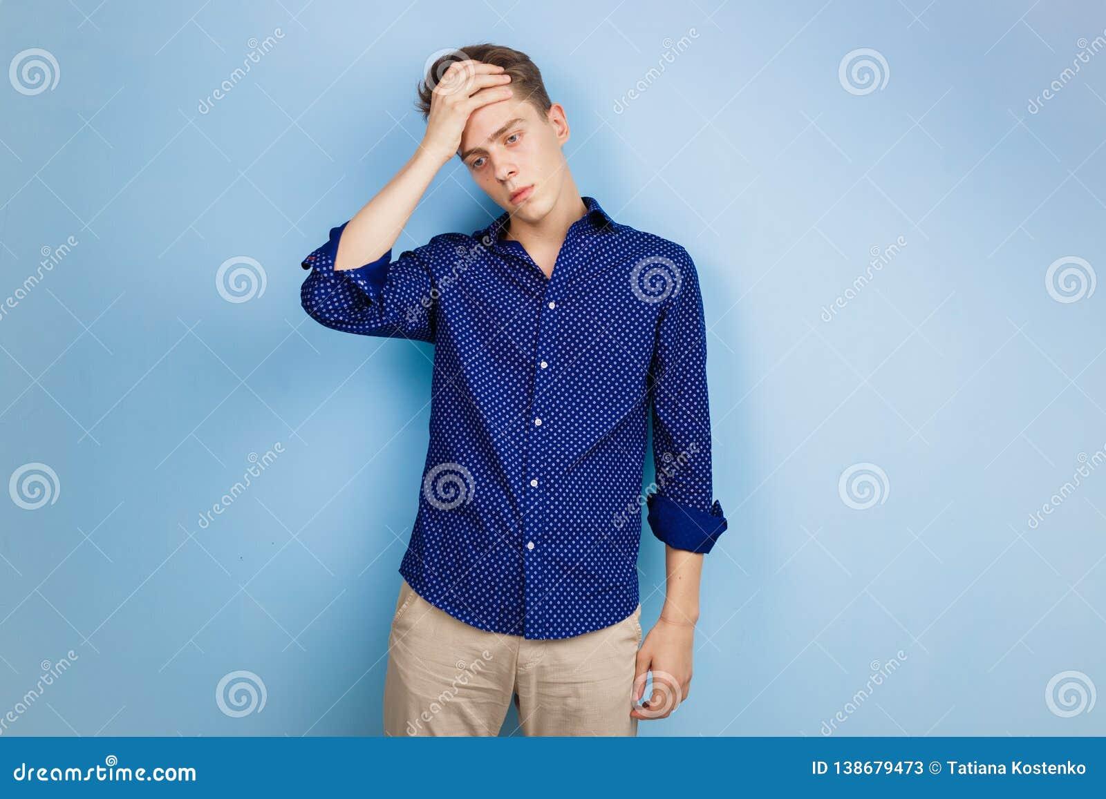 Ανατρέψτε το νεαρό άνδρα στο μπλε πουκάμισο, κρατώντας το χέρι στο μέτωπο, ξεχνώντας κάτι ή αισθαμένος τη θλίψη, που στέκεται πέρ