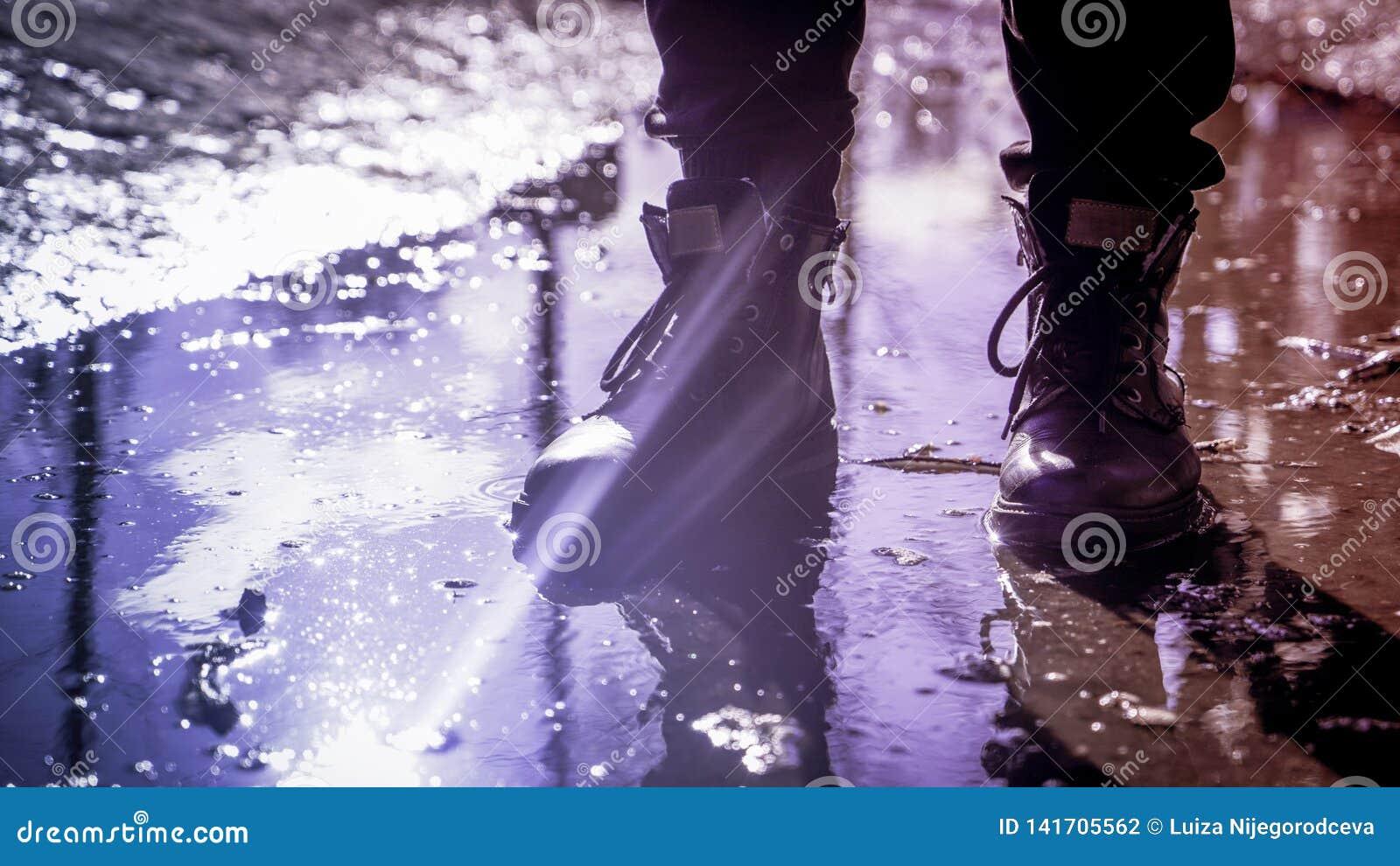 Ανθρώπινα πόδια στις μοντέρνες μπότες που στέκονται στη λακκούβα