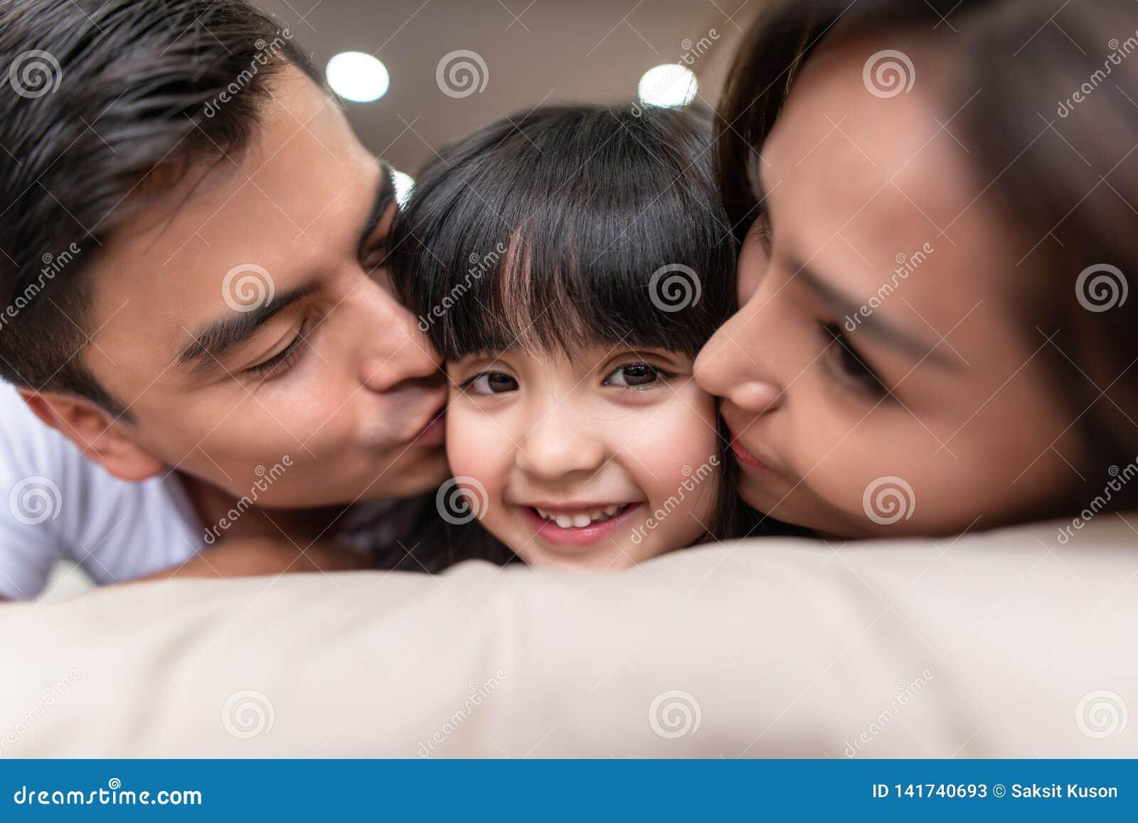 Ασιατικοί γονείς που φιλούν τη μικρή κόρη τους και στα δύο μάγουλα