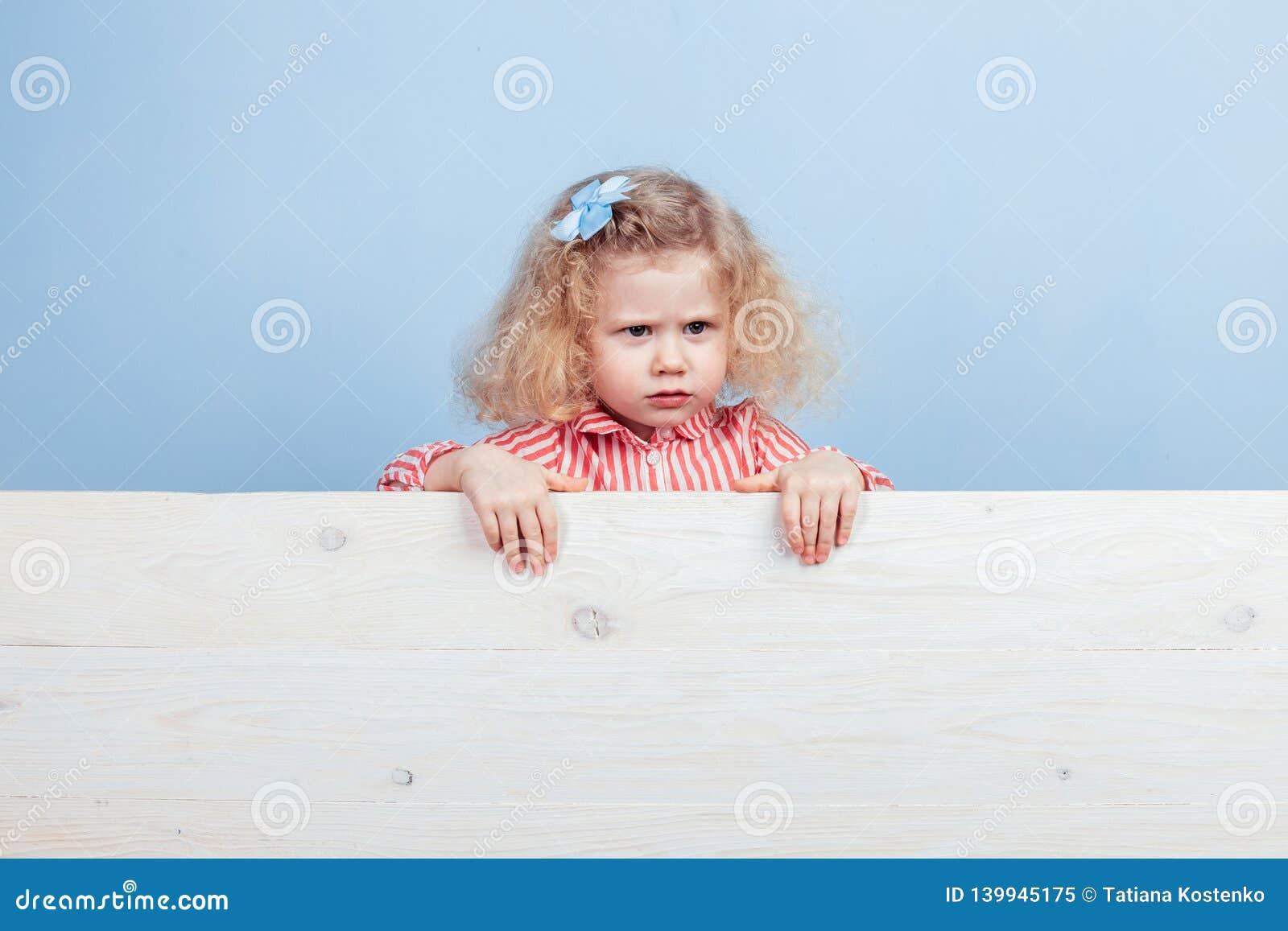 Αστείο λίγο σγουρό κορίτσι σε ένα ριγωτό κόκκινο και άσπρο φόρεμα και ένα μπλε λουλούδι στην τρίχα της στέκεται πίσω από τον ξύλι