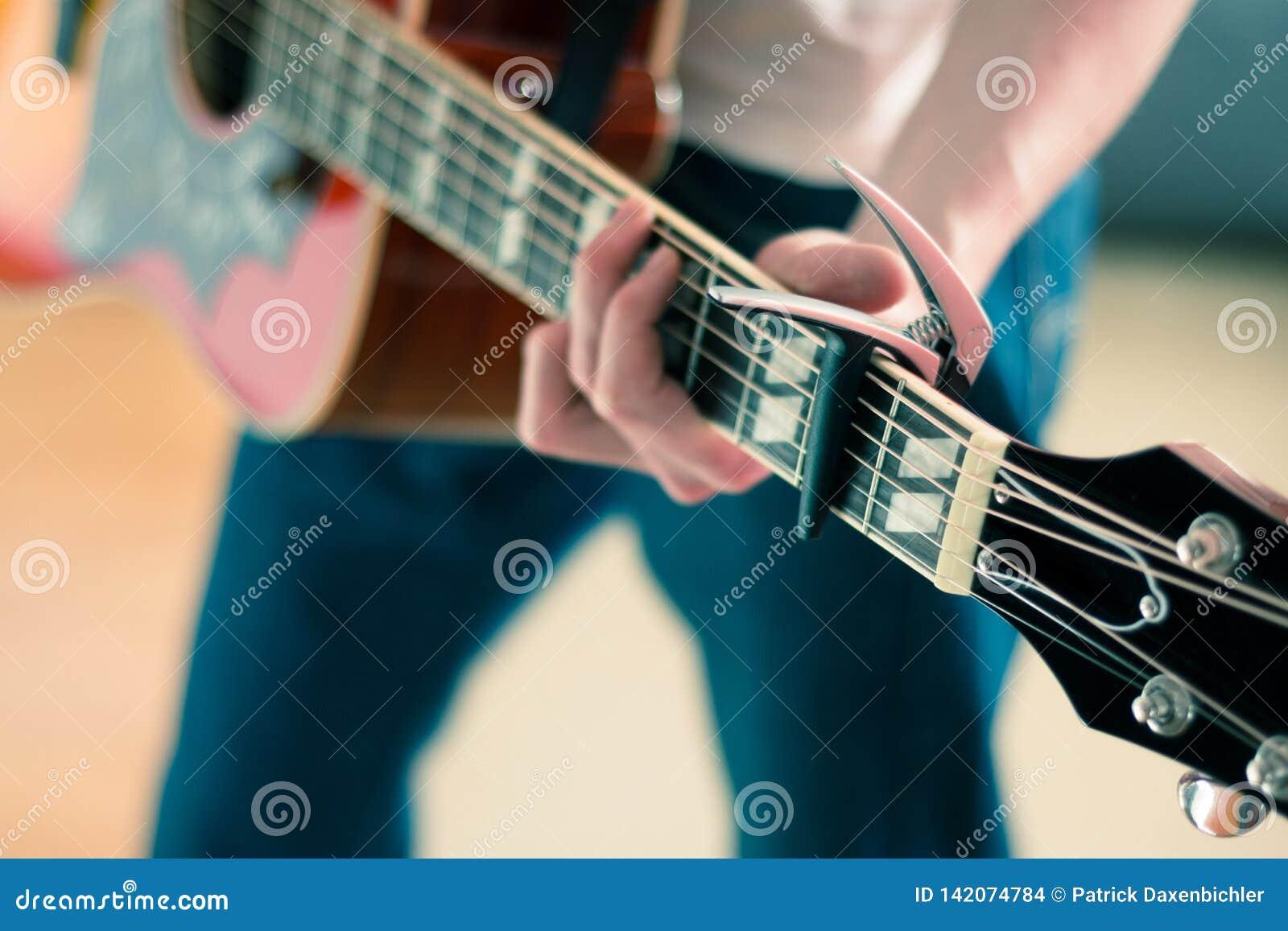 Αποκόπτω ενός νεαρού άνδρα που παίζει μια δυτική κιθάρα ηλιοφάνειας