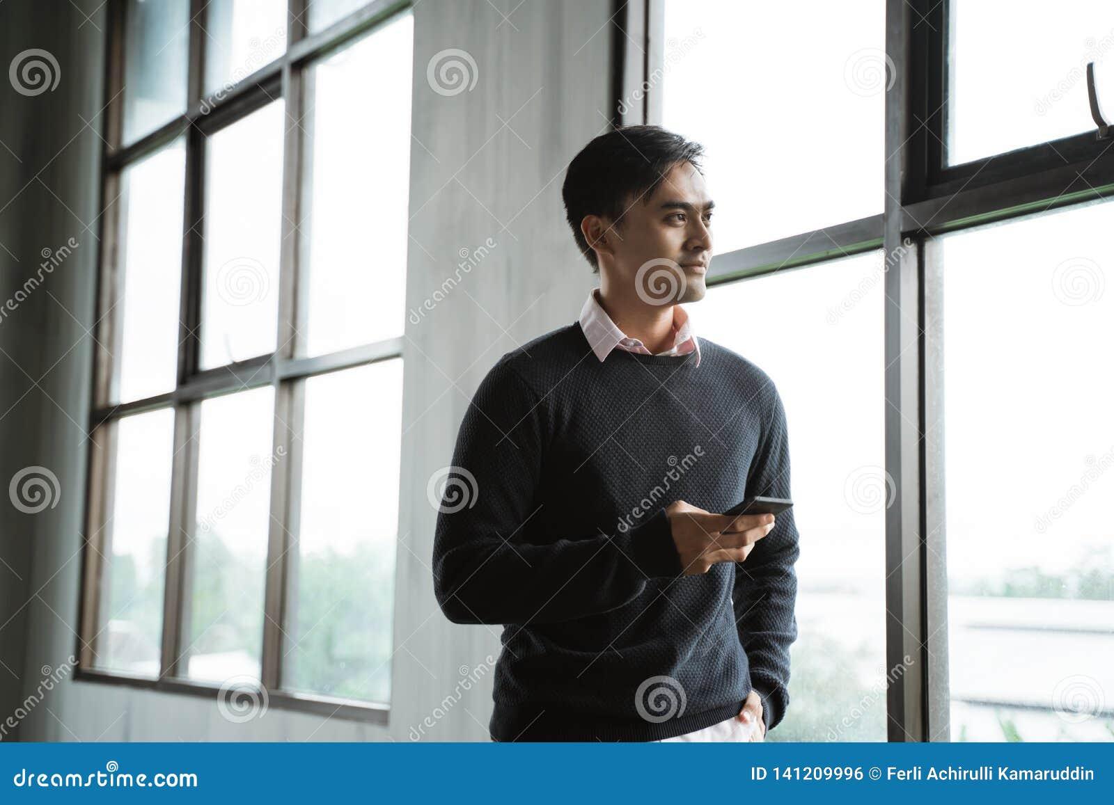 Βέβαιος νέος επιχειρηματίας που χρησιμοποιεί το τηλέφωνο κυττάρων