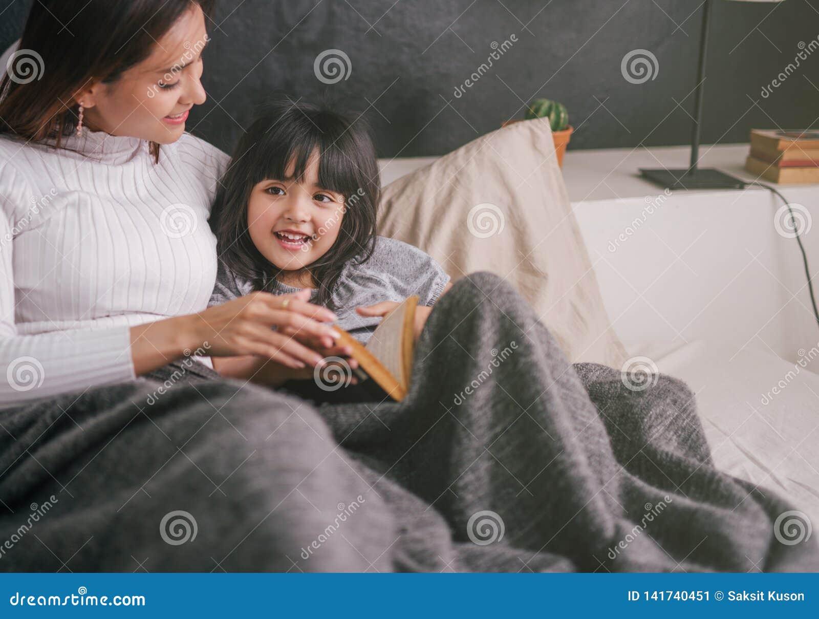 Βιβλίο ανάγνωσης μητέρων και κορών στο σπίτι στην κρεβατοκάμαρα