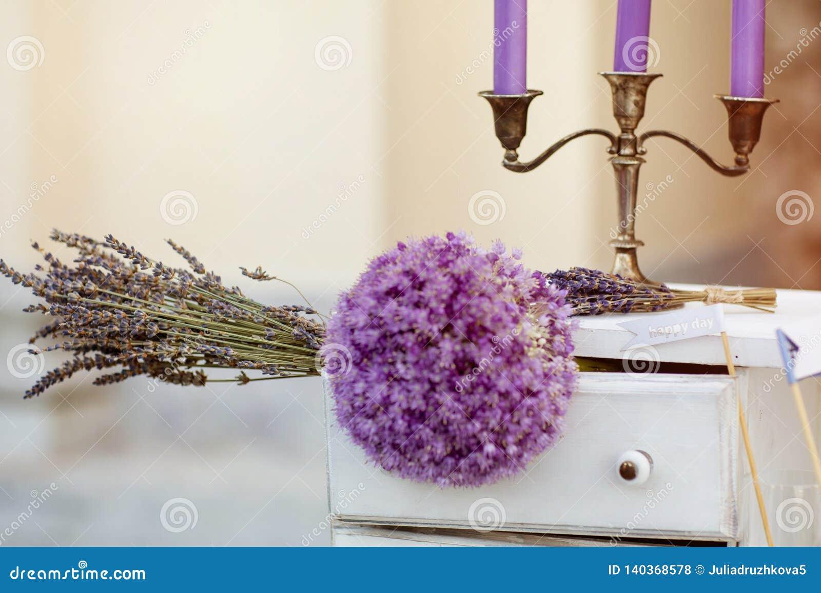 Γαμήλια ανθοδέσμη, μπλε κεριά με ένα κηροπήγιο και γυαλιά με τη σαμπάνια lavender ανθοδέσμη που βρίσκεται στον πίνακα στο υπόβαθρ