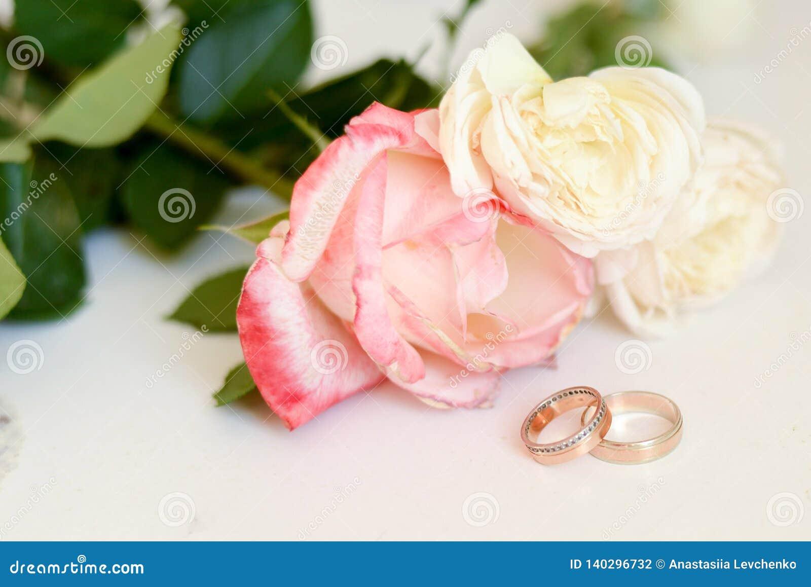 Γαμήλια δαχτυλίδια στο υπόβαθρο λουλουδιών