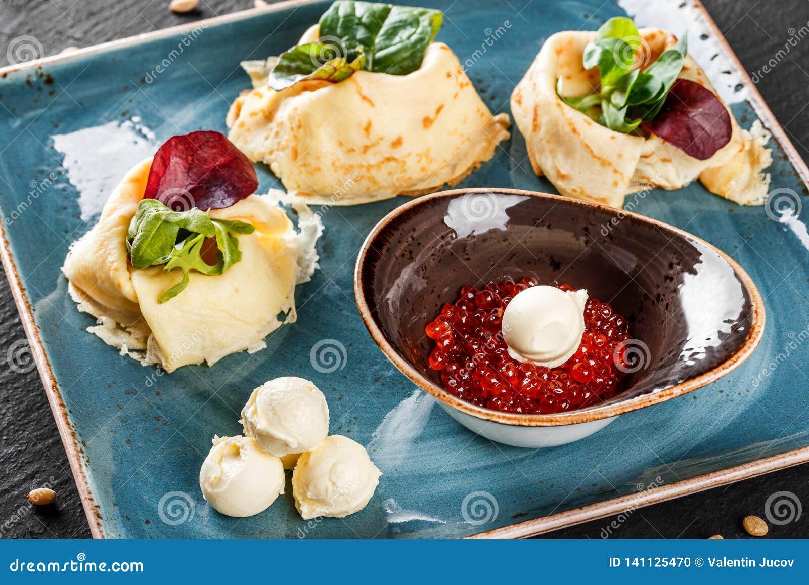 Γεμισμένος crepes ολοκληρωμένος με το κόκκινο χαβιάρι, το βούτυρο και τα πράσινα στο πιάτο Άποψη σχετικά με μια σκοτεινή γκρίζα ε