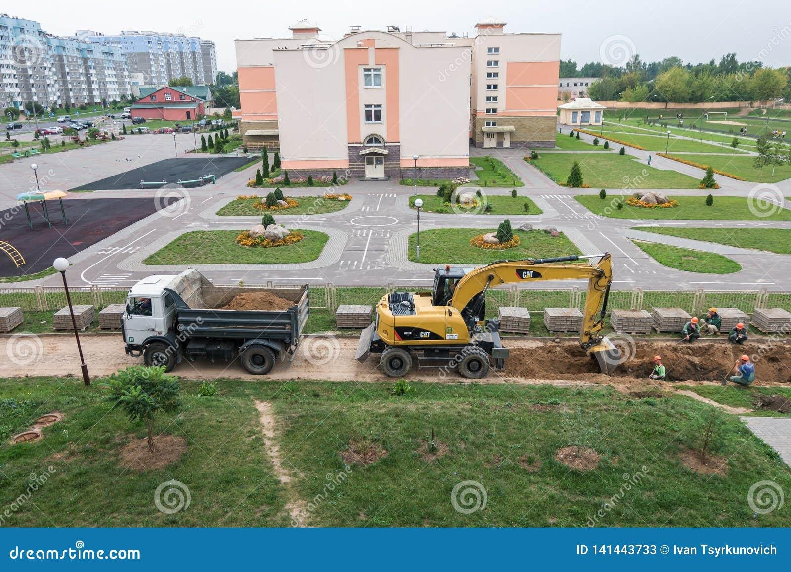 ΓΚΡΟΝΤΝΟ, ΛΕΥΚΟΡΩΣΙΑ - ΤΟ ΣΕΠΤΈΜΒΡΙΟ ΤΟΥ 2018: Ο εκσκαφέας σκάβει ένα κοίλωμα και φορτώνει την άμμο σε ένα φορτηγό απορρίψεων