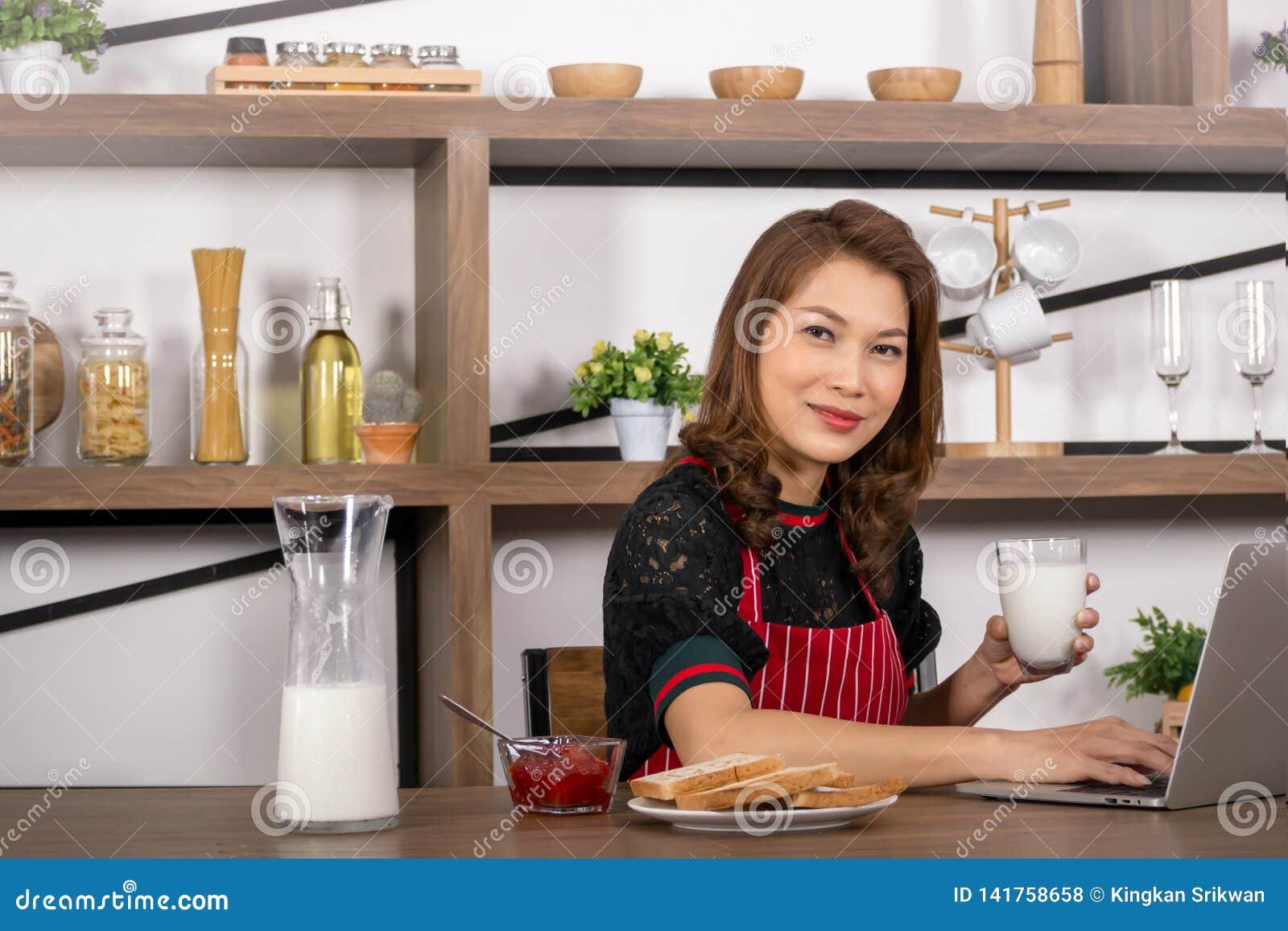 Γυναίκα που κρατά ένα ποτήρι του γάλακτος και που χρησιμοποιεί το lap-top