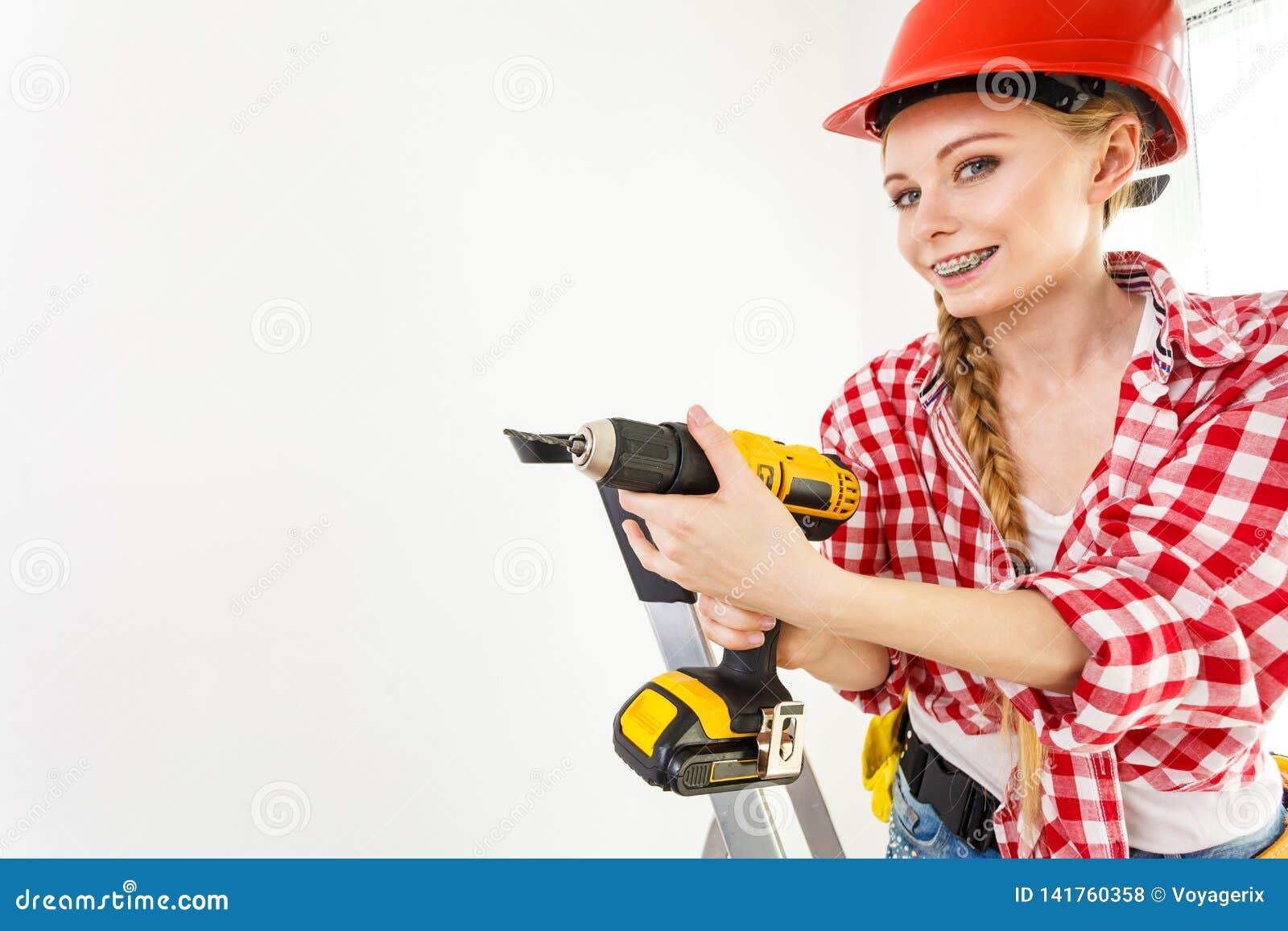 Γυναίκα που χρησιμοποιεί το τρυπάνι στη σκάλα