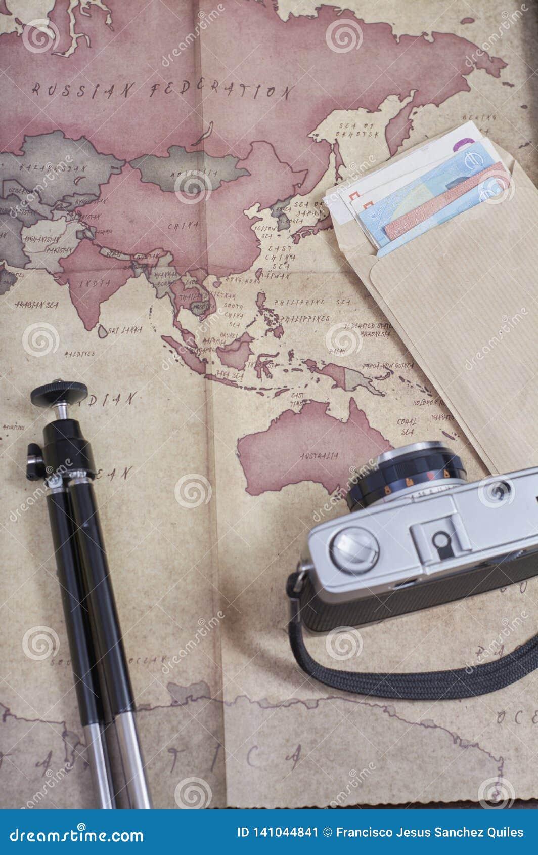 Εκλεκτής ποιότητας φωτογραφική κάμερα δίπλα σε έναν χάρτη, ένα τρίποδο και έναν φάκελο των χρημάτων σε ευρώ που προετοιμάζουν ένα