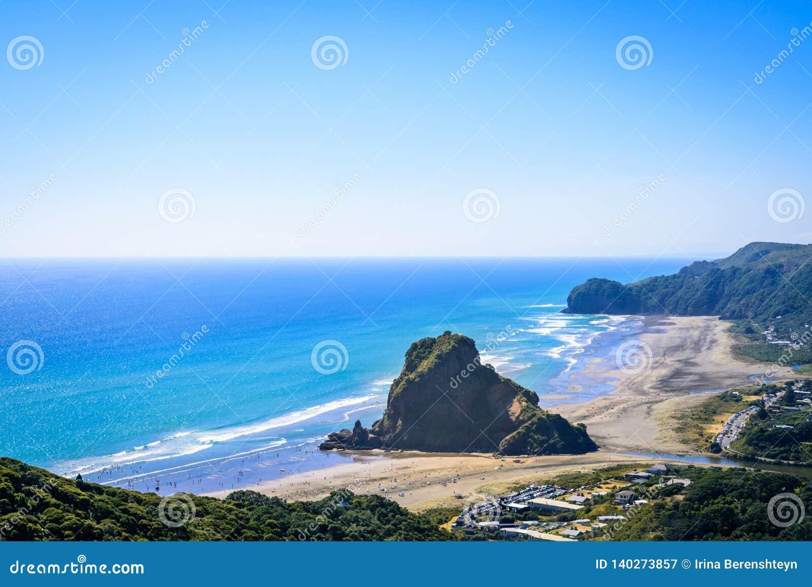 Εναέρια άποψη πέρα από την παραλία Piha, δυνατός βράχος λιονταριών στο κέντρο, στη δυτική ακτή του Ώκλαντ, Νέα Ζηλανδία