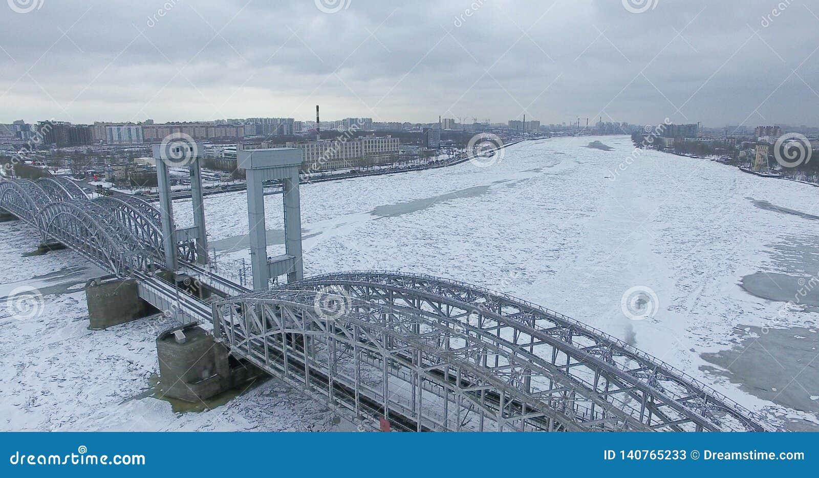 εναέρια όψη Πέταγμα κατά μήκος του ποταμού Neva στο χειμερινό συννεφιάζω κρύο καιρό Γέφυρα πέρα από τον ποταμό Πετρούπολη Το ύψος