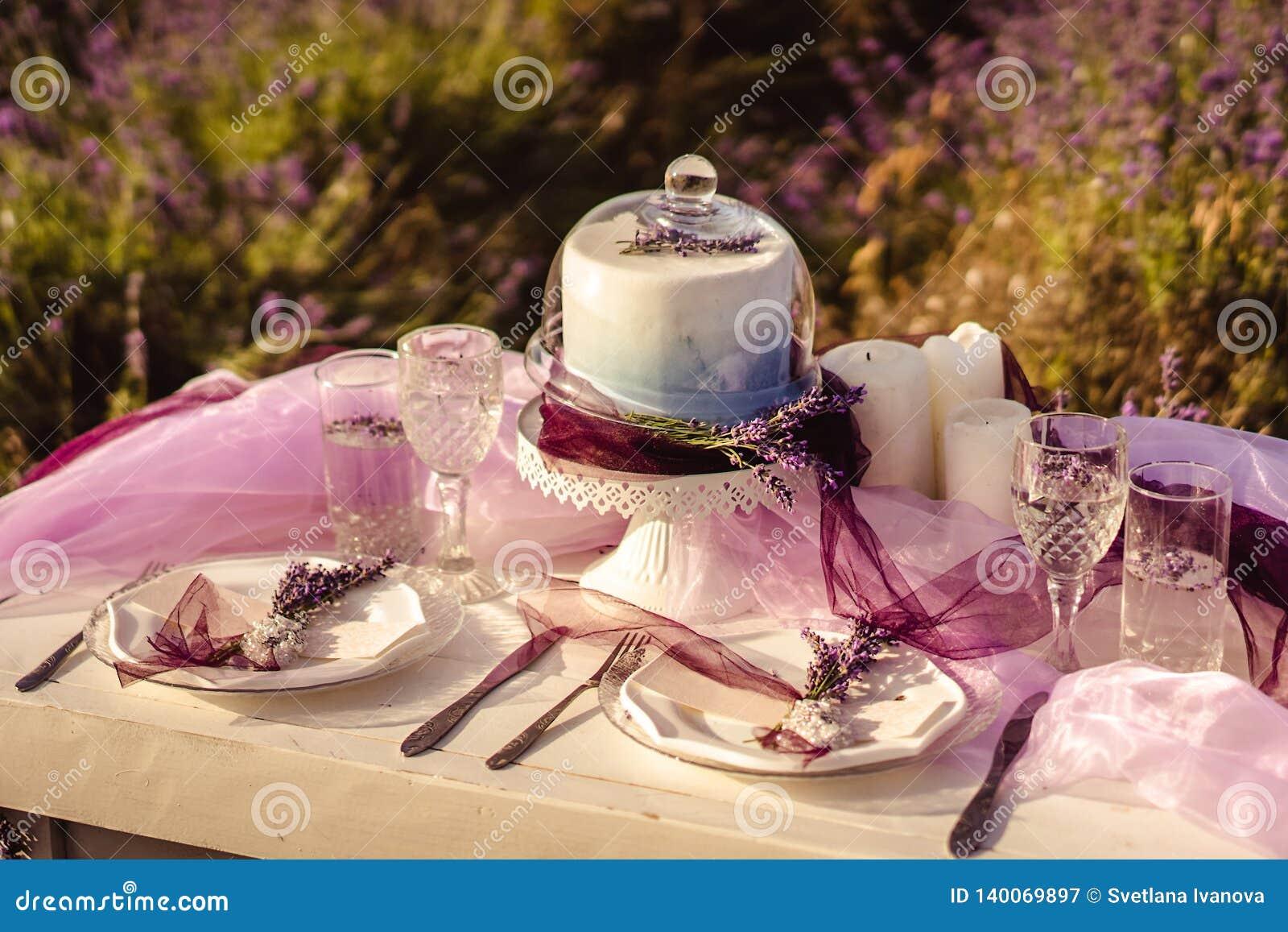 Εξυπηρετούμενος Festively πίνακας με lavender τις ανθοδέσμες και το κέικ