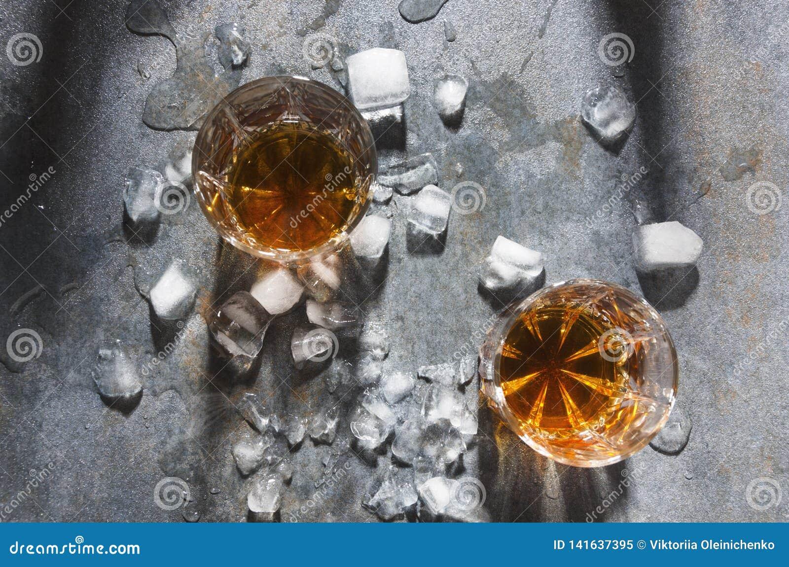 Εορτασμός στο φραγμό Ζευγάρι των γυαλιών με τα ποτά οινοπνεύματος και τους κύβους πάγου, τοπ άποψη Γυαλιά με το ουίσκυ που εξυπηρ