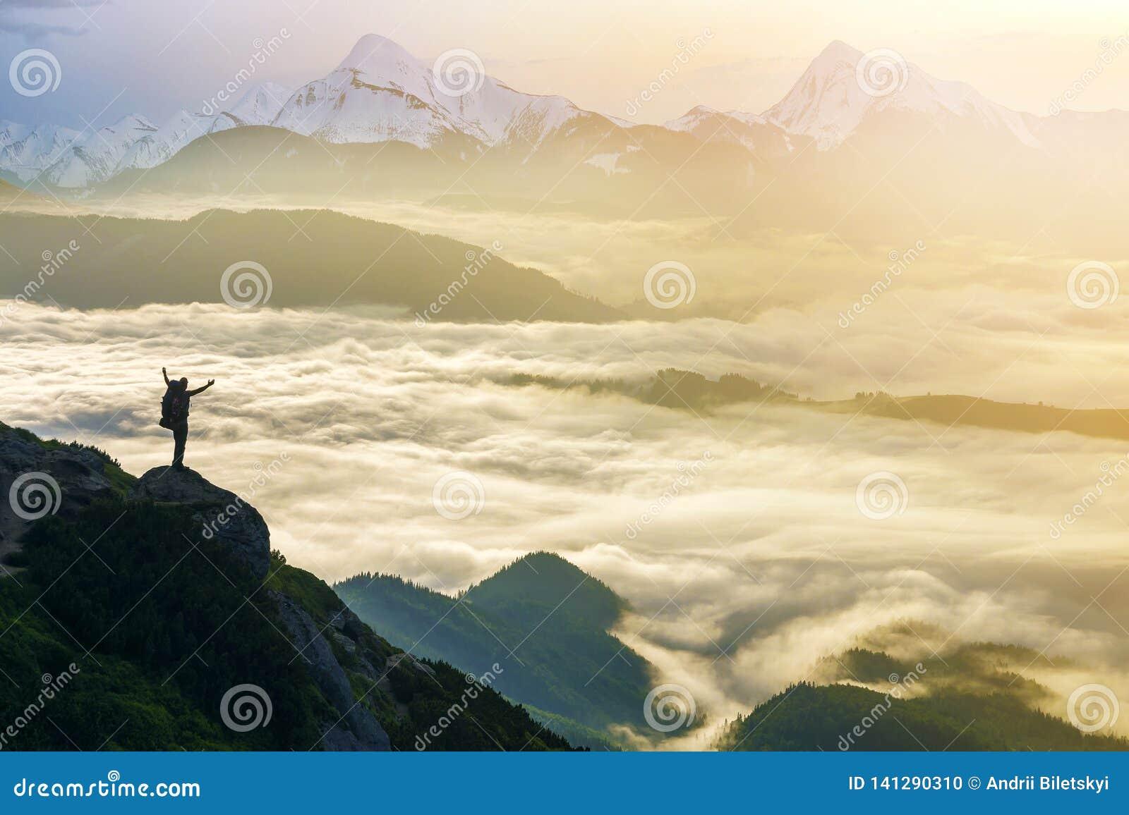 Ευρύ πανόραμα βουνών Η μικρή σκιαγραφία του τουρίστα με το σακίδιο πλάτης στη δύσκολη βουνοπλαγιά με αυξημένος παραδίδει την κοιλ