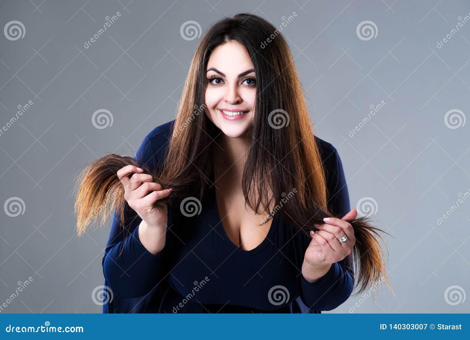 Ευτυχές brunette συν την πρότυπη, παχιά γυναίκα μεγέθους με τις μακρυμάλλεις και διασπασμένες άκρες στο γκρίζο υπόβαθρο