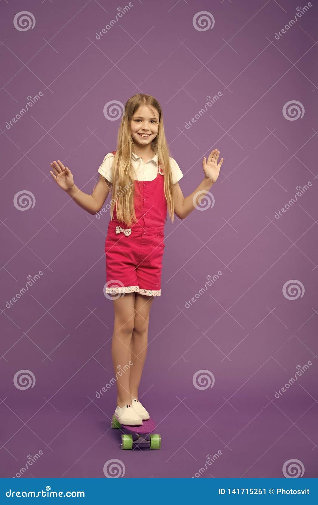 Ευτυχές skateboard γύρου κοριτσιών στο ιώδες υπόβαθρο Λίγο παιδί στον πίνακα πενών Ανάπτυξη και ευτυχία παιδικής ηλικίας