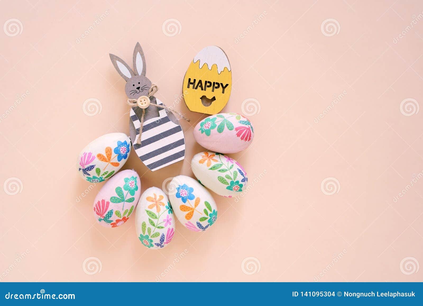 Ευτυχής έννοια Πάσχας με το ξύλινο λαγουδάκι και τα ζωηρόχρωμα αυγά Πάσχας στο κίτρινο υπόβαθρο