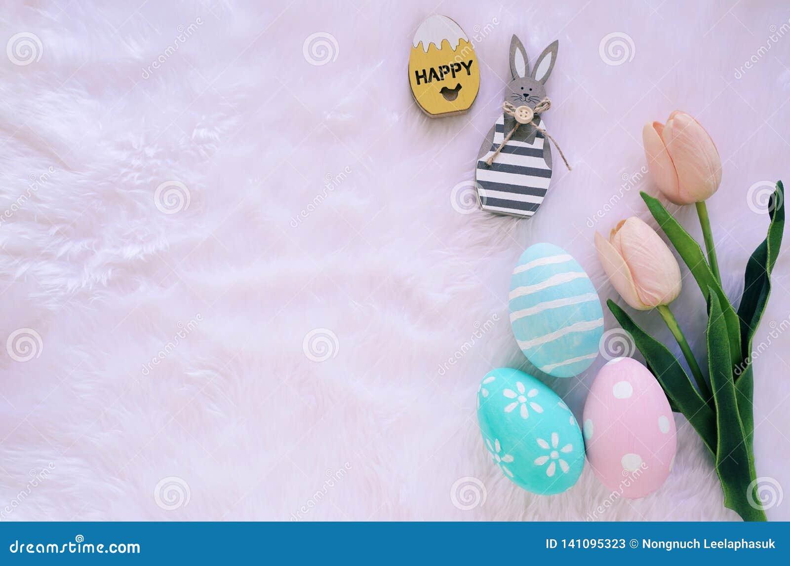 Ευτυχής έννοια Πάσχας με το ξύλινο λαγουδάκι και τα ζωηρόχρωμα αυγά Πάσχας στο άσπρο υπόβαθρο γουνών και τις ρόδινες τουλίπες