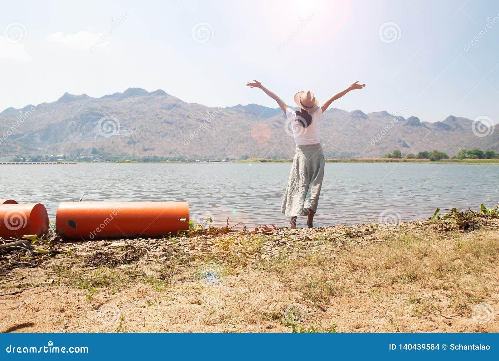 Ευτυχής ασιατική γυναίκα στον περιστασιακό ιματισμό ύφους που αυξάνεται επάνω στα όπλα και στάση στον ποταμό με τη θέα βουνού