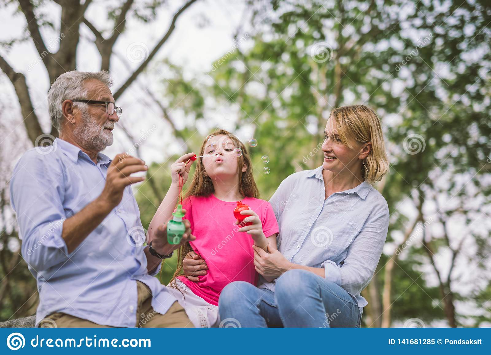 Ευτυχής οικογένεια στο πράσινο πάρκο φύσης στο καλοκαίρι