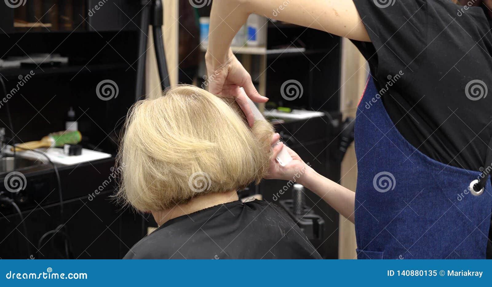 Επαγγελματικός κομμωτής, στιλίστας που κτενίζει την τρίχα του θηλυκού πελάτη και την τέμνουσα τρίχα στο επαγγελματικό κομμωτήριο