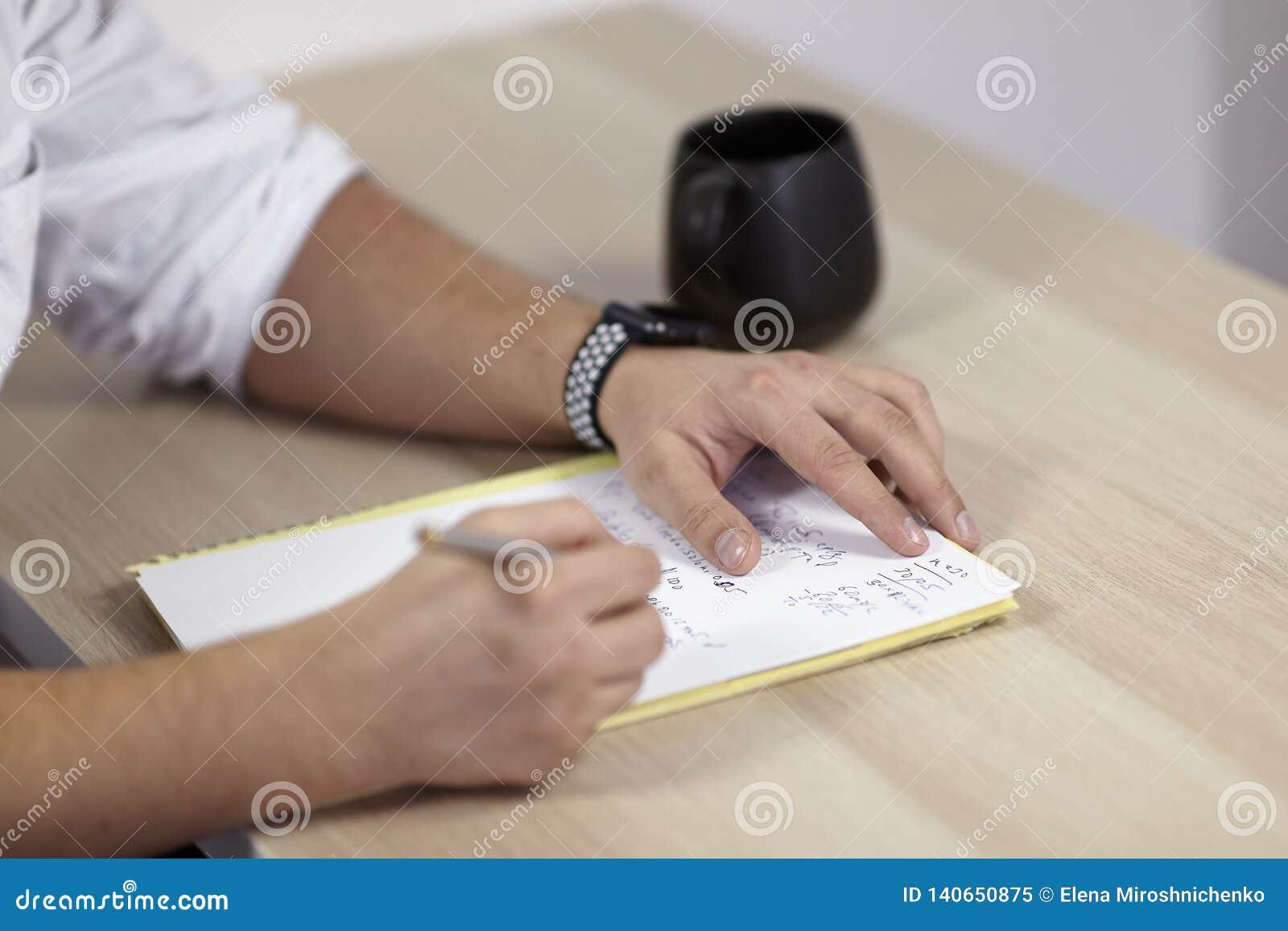 Επανδρώνει τα χέρια στην άσπρη εξάρτηση γράφει με τη μάνδρα κυλίνδρων σε χαρτί για τον ξύλινο πίνακα κάποια λατινικά, ή τους όρου
