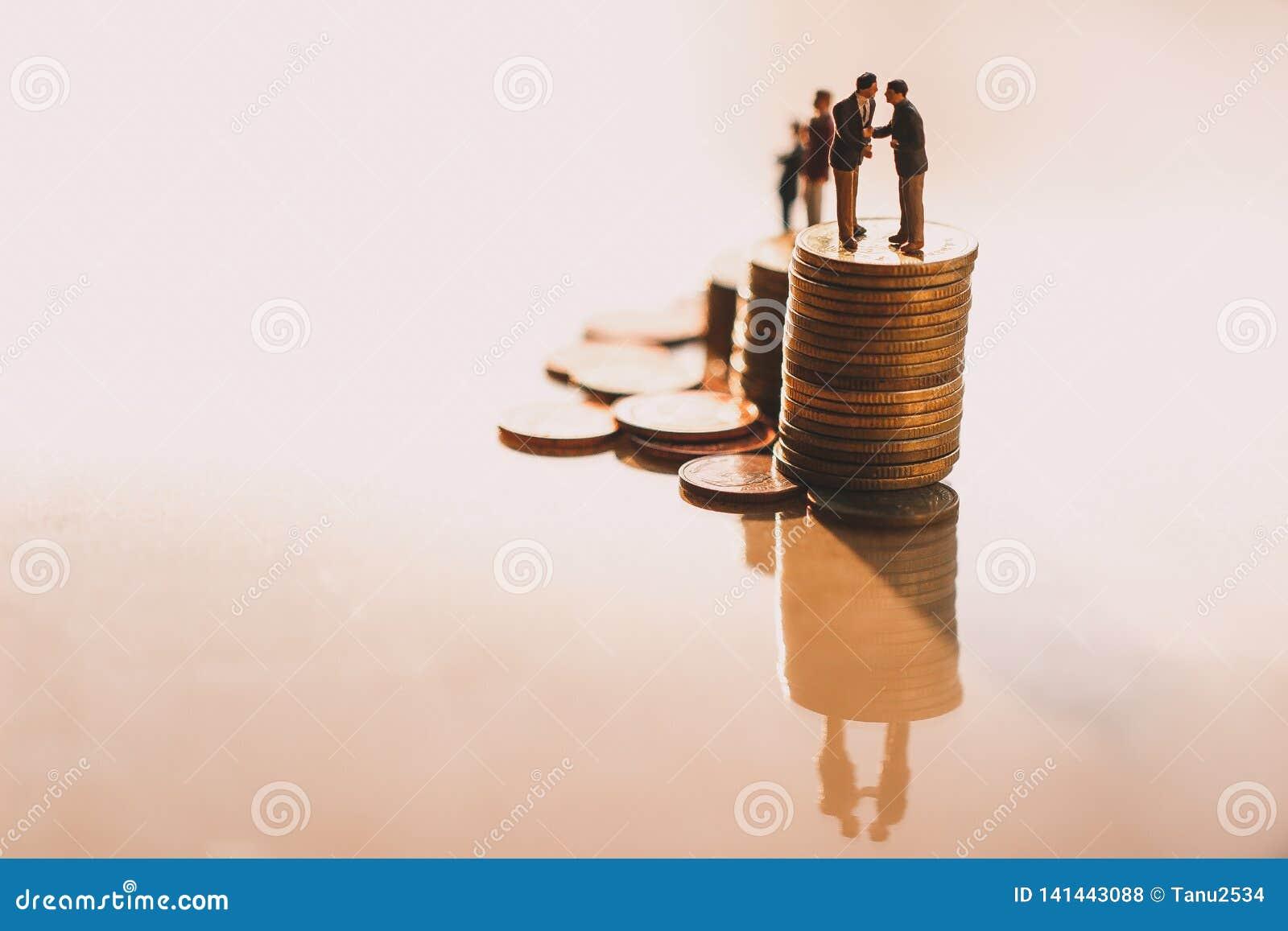 Επιχειρηματίες που ελέγχουν το χέρι στους σωρούς νομισμάτων