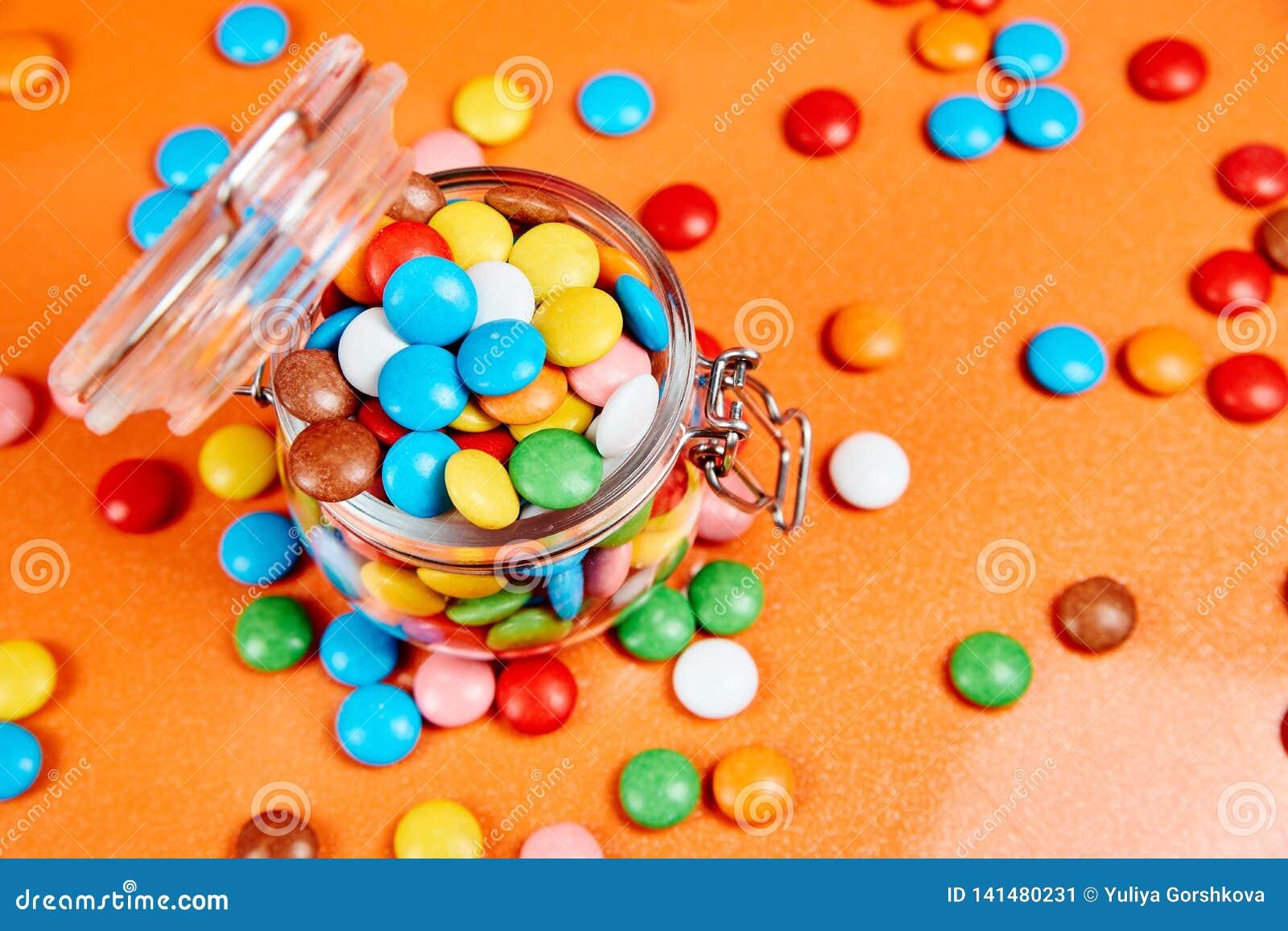 Ζωηρόχρωμες καραμέλες στο βάζο γυαλιού στο κόκκινο υπόβαθρο πορτοκαλιών