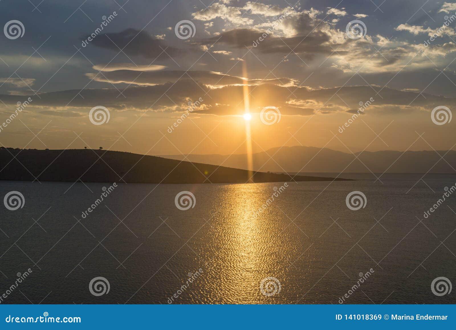 Ηλιοβασίλεμα πέρα από τη θάλασσα και τα νησιά