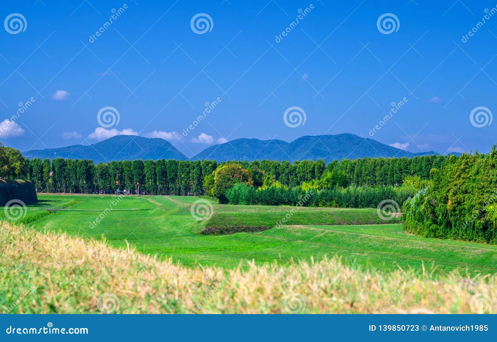 Η άποψη του πράσινου τομέα χλόης, τα δέντρα και οι λόφοι και τα βουνά της Τοσκάνης με το σαφές αντίγραφο μπλε ουρανού χωρίζουν κα