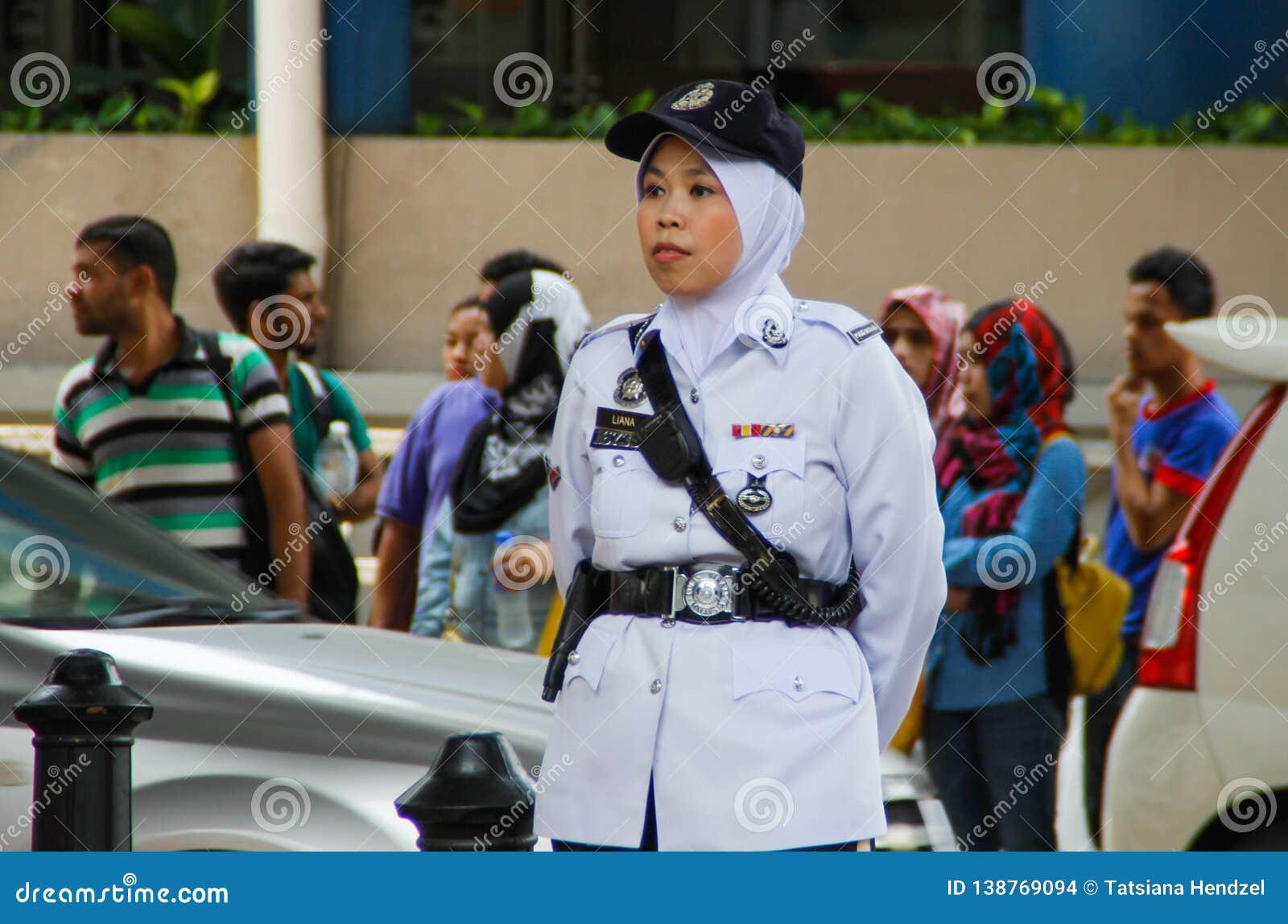 Η ασιατική γυναίκα αστυνομίας στέκεται κατά μήκος του δρόμου άσπρους σε έναν ομοιόμορφο, μια ΚΑΠ και hijab